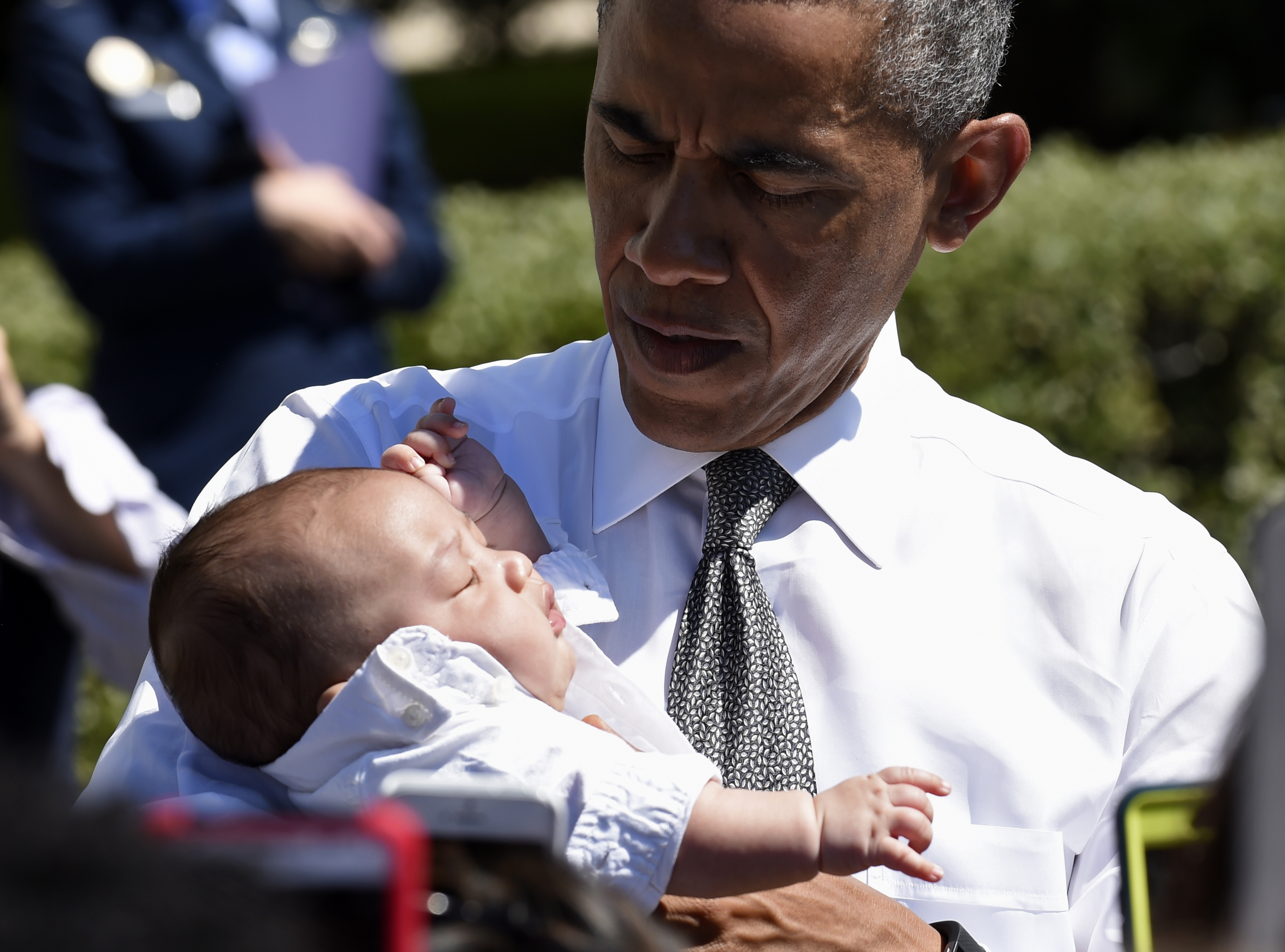 President Barack Obama holds a baby as he greets guests attending an event at the White House in Washington on April 16, 2015.