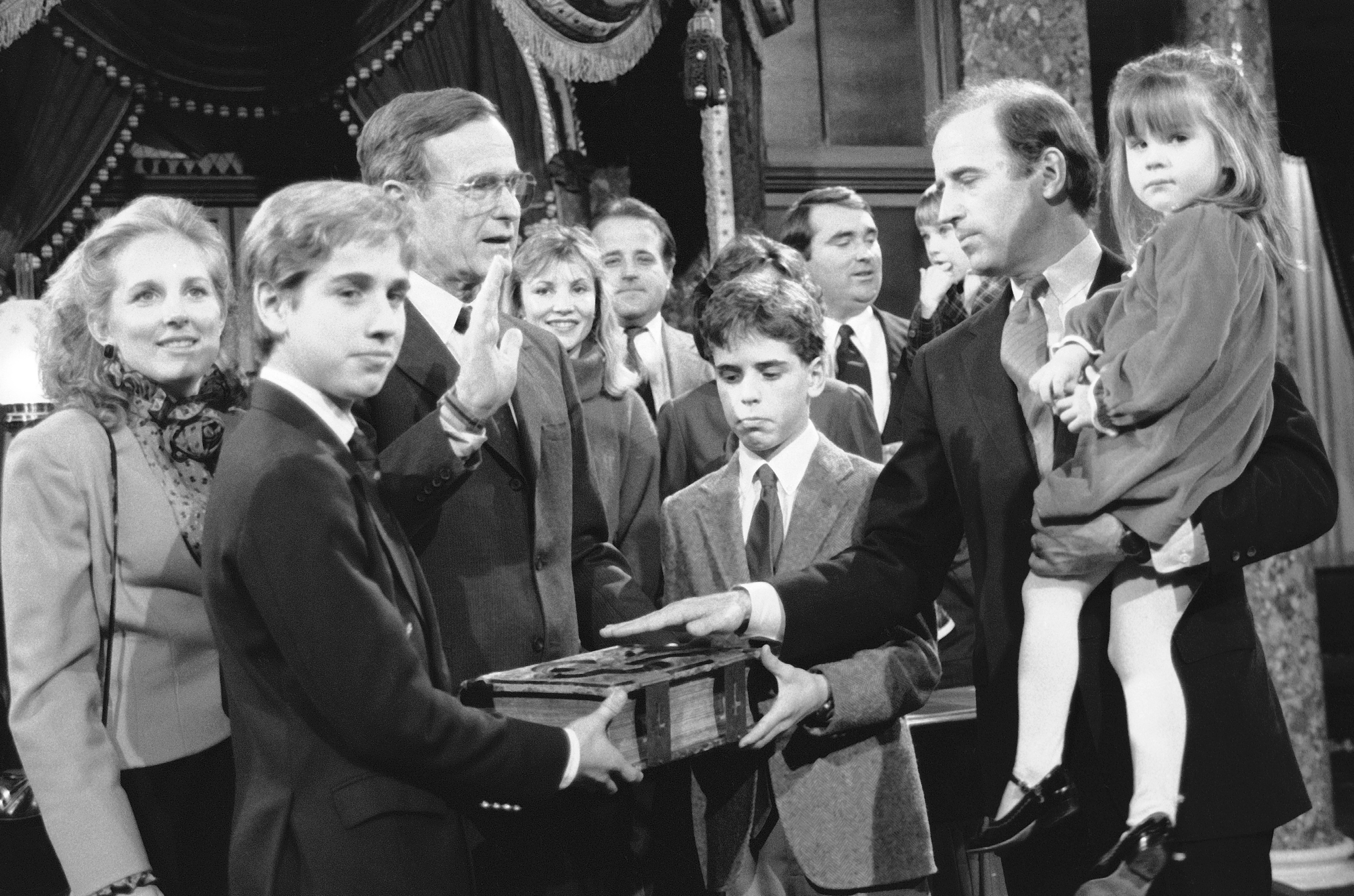 Joe Biden takes a mock oath of office from George H. W. Bush, accompanied by his family in Capitol Hill in Washington on Jan. 3, 1985.