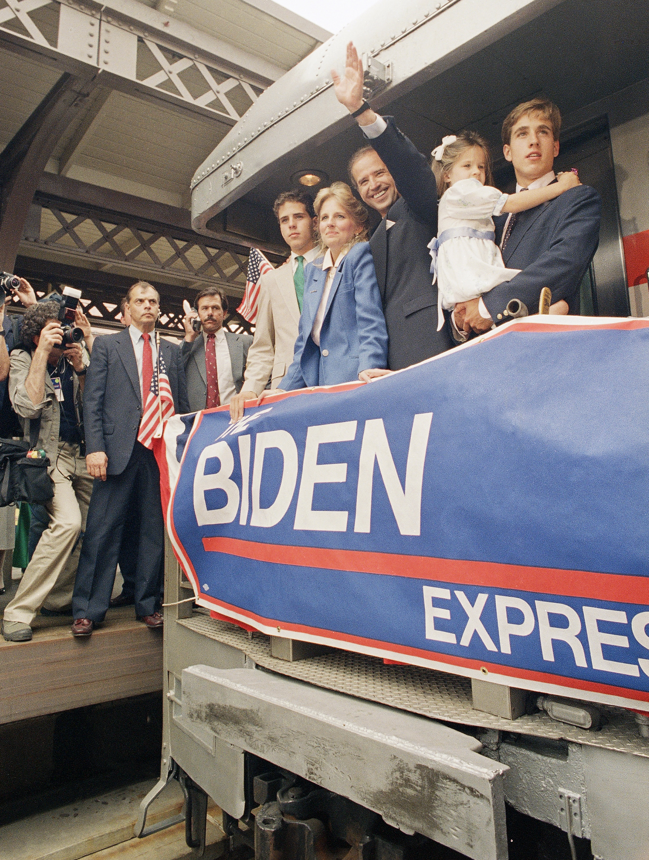 Senator Joseph Biden, (D-Del.), center, waves to a crowd as his train leaves, after he announced his candidacy for President in Wilmington, Del., June 9, 1987. At right, Biden's son, Beau, carries Biden's daughter Ashley. Next to Biden is his wife, Jill, and son Hunter.