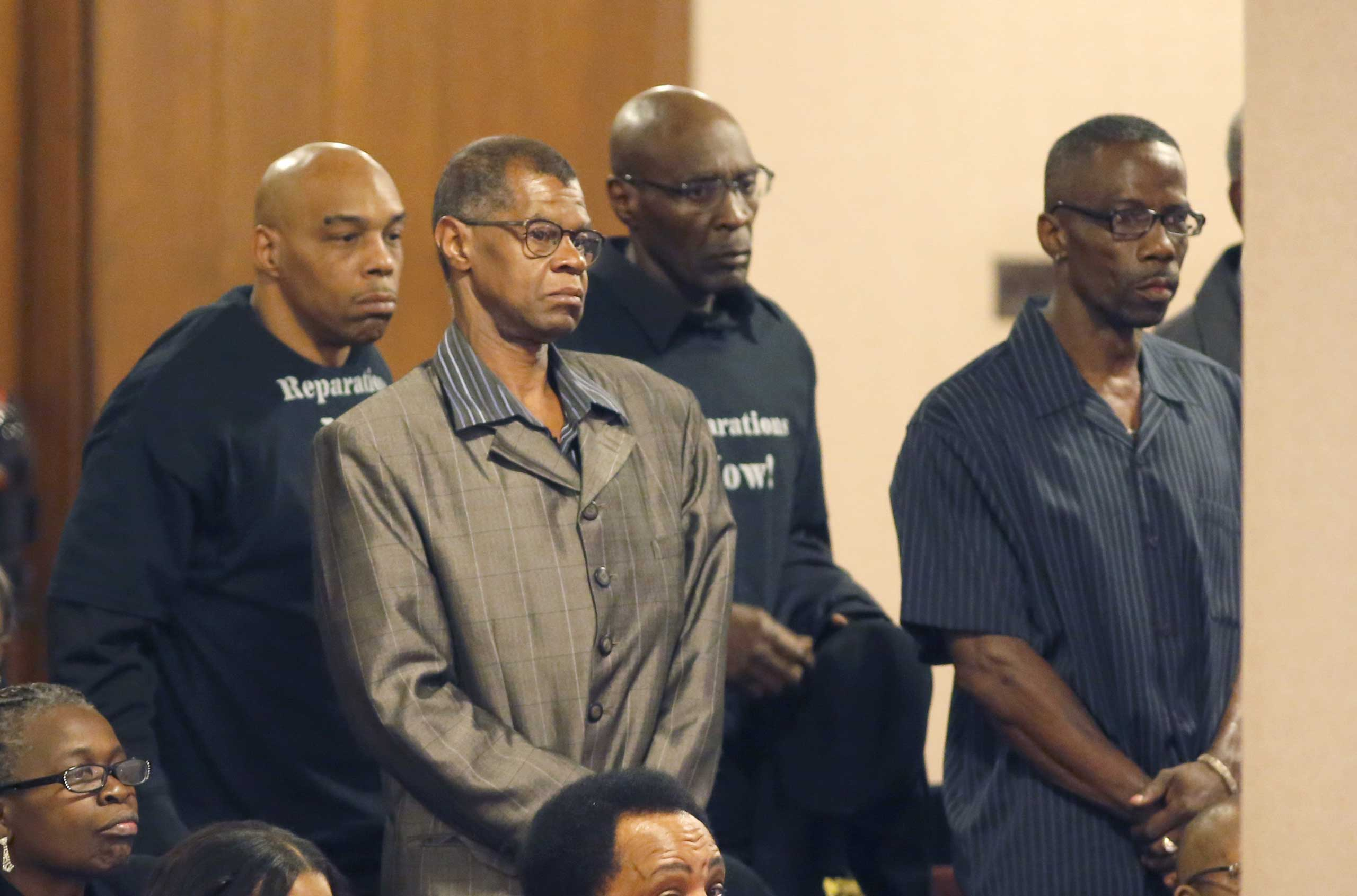 Men identified as victims of police torture under the command of retired Chicago Police Commander Jon Burge, stand to be recognized by the Chicago City Council city council, May 6, 2015, in Chicago.