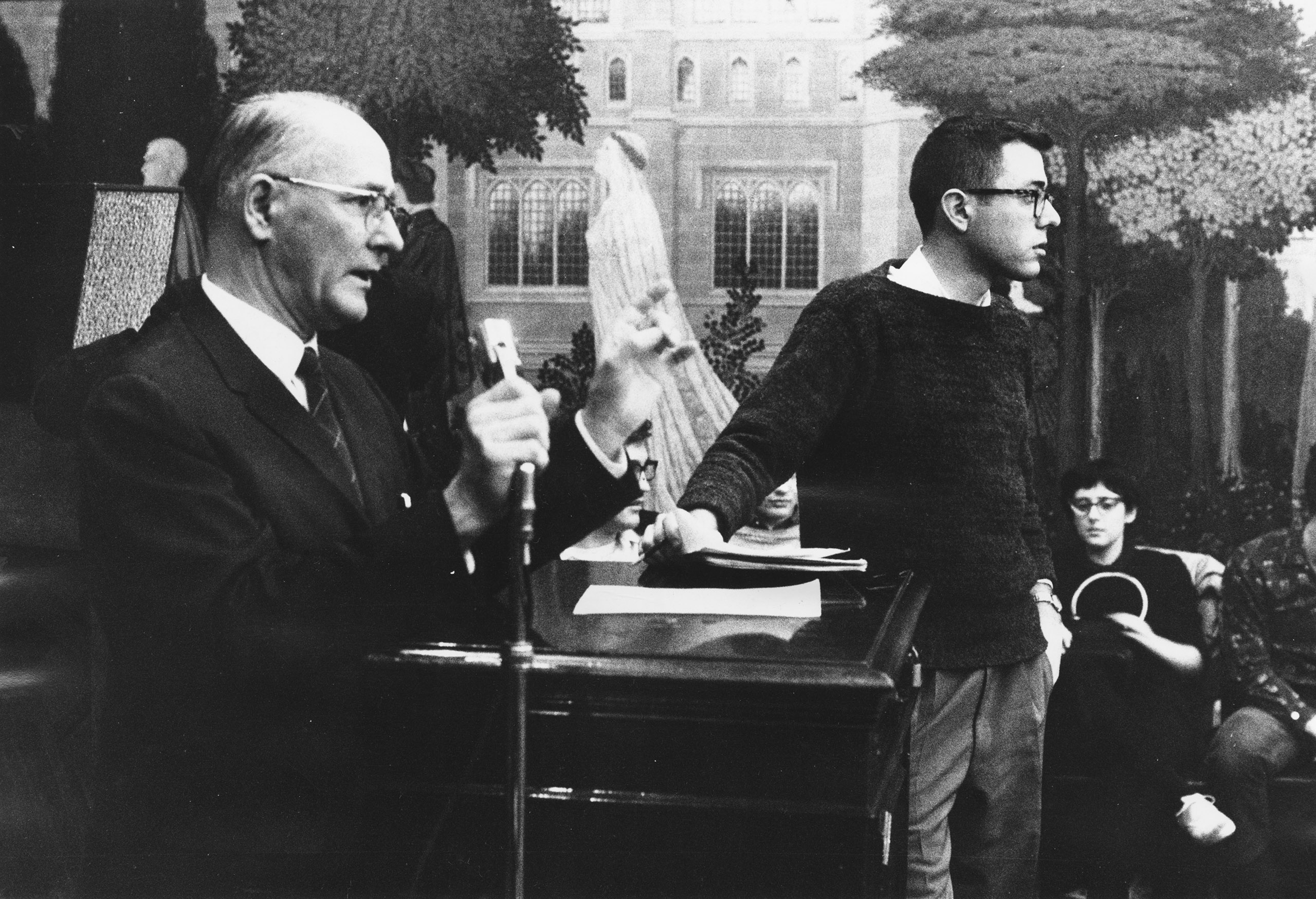 Bernie Sanders (R), member of the steering committee, stands next to George Beadle, University of Chicago president, who is speaking at a Committee On Racial Equality meeting on housing sit-ins. 1962.