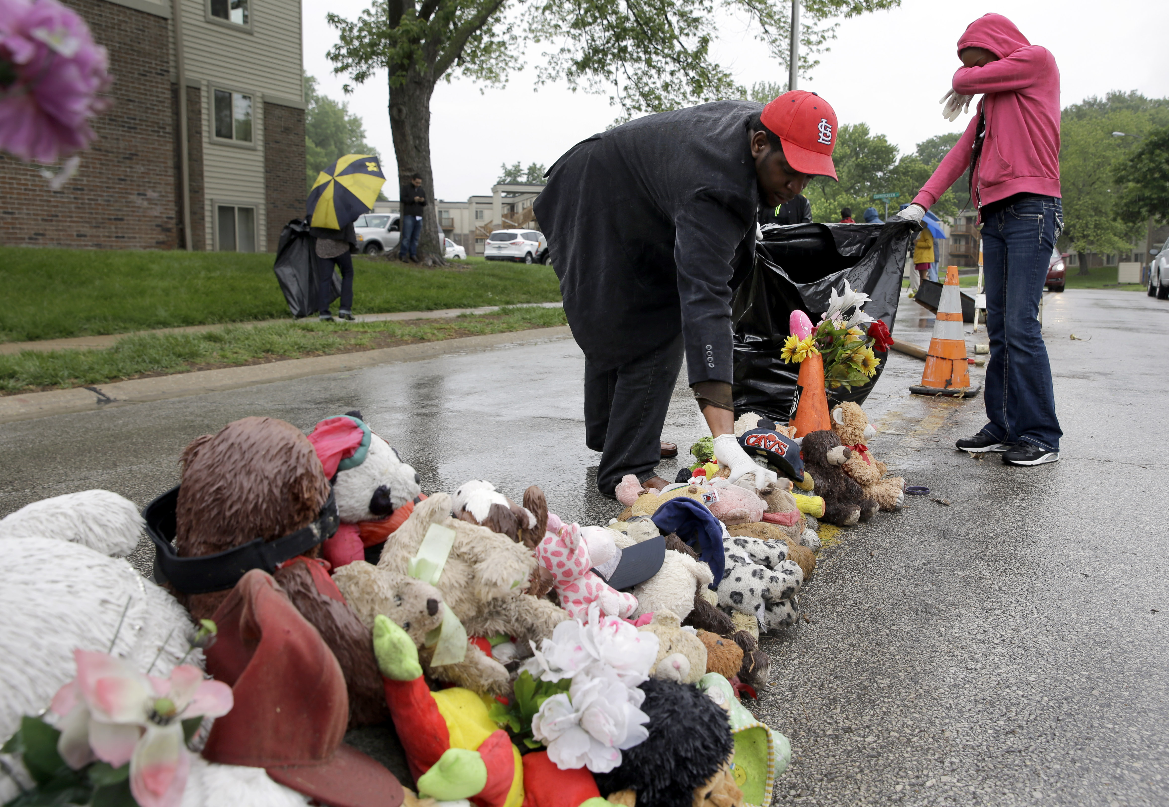 Volunteers Cheyenne Green, right, and Derrick Robinson help remove items left at a makeshift memorial to Michael Brown Wednesday, May 20, 2015, in Ferguson, Mo.