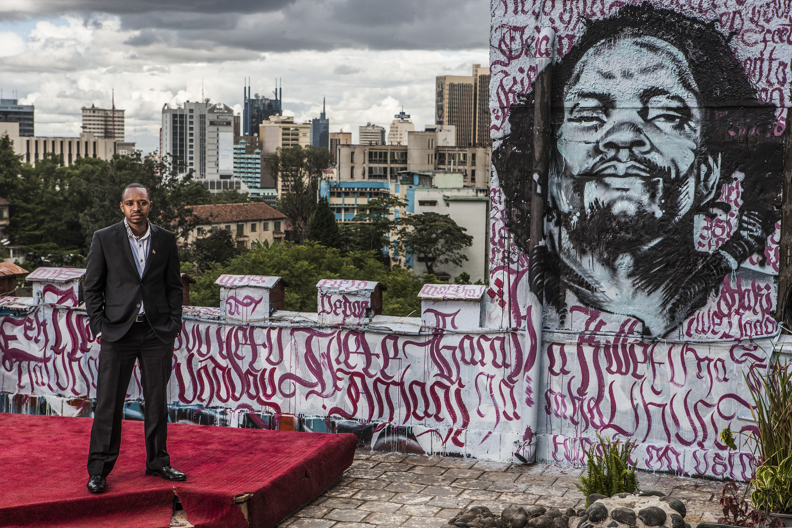 Kenyan Political activist Boniface Mwangi stands for a portrait on the roof of Pawa254, an organization he founded, in Nairobi, Kenya. He stands opposite a graffiti portrait of Dedan Kimathi, a leader of the Mau Mau rebellion against British colonial rule in Kenya. Kimathi was jailed and eventually executed by the colonial administration. Mwangi claims that Kimathi is one of his idols. Boniface started as a photographer but has now morphed into a controversial political activist who uses various forms of art in his protests.