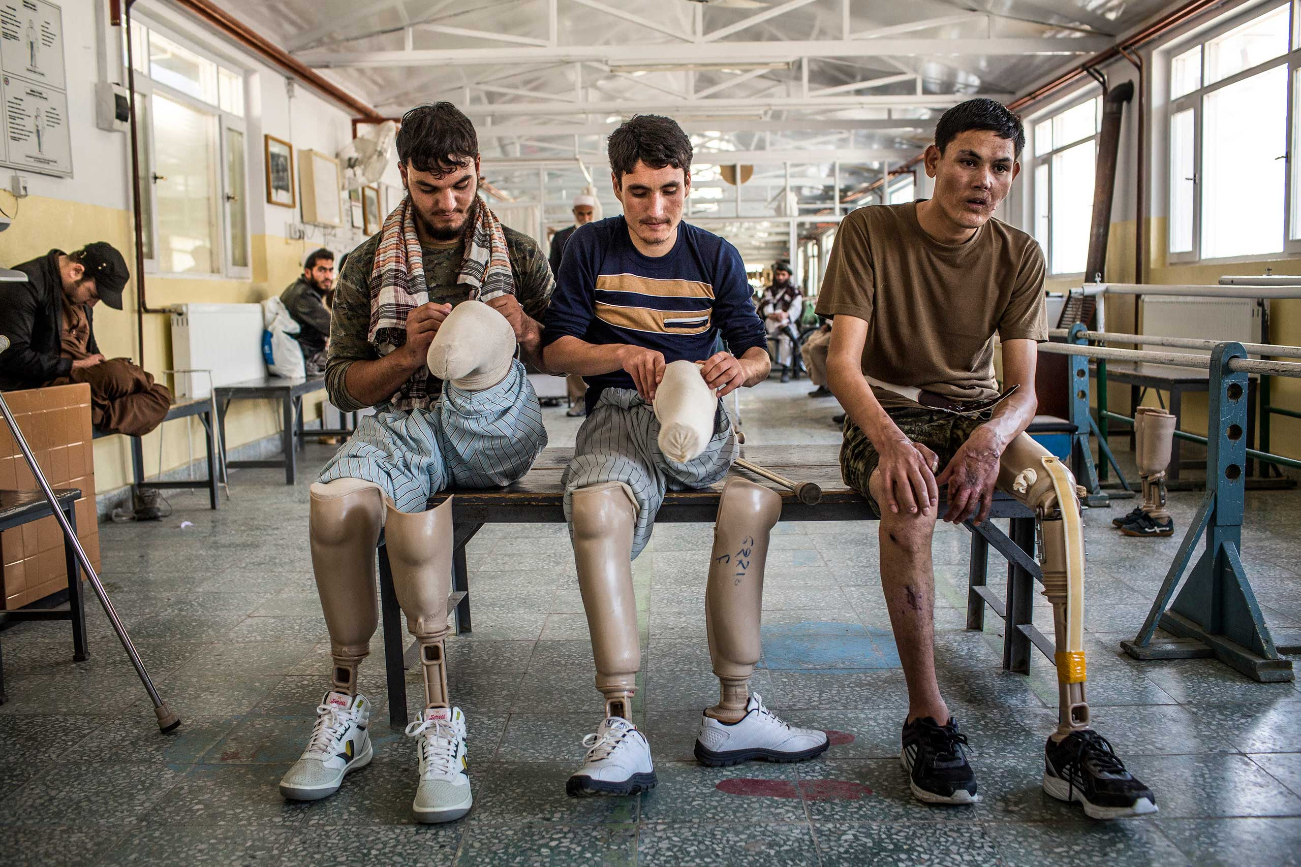 The New York Times: Disabled and Facing More Challenges in Afghanistan                               Rahimullah, Hamza and Islamudding, Afghan National Army soldiers who had injuries and amputations, adjust their prosthetics between physiotherapy sessions at the International Committee of the Red Cross?s orthopedic center in Kabul, Afghanistan, Nov. 22, 2014.