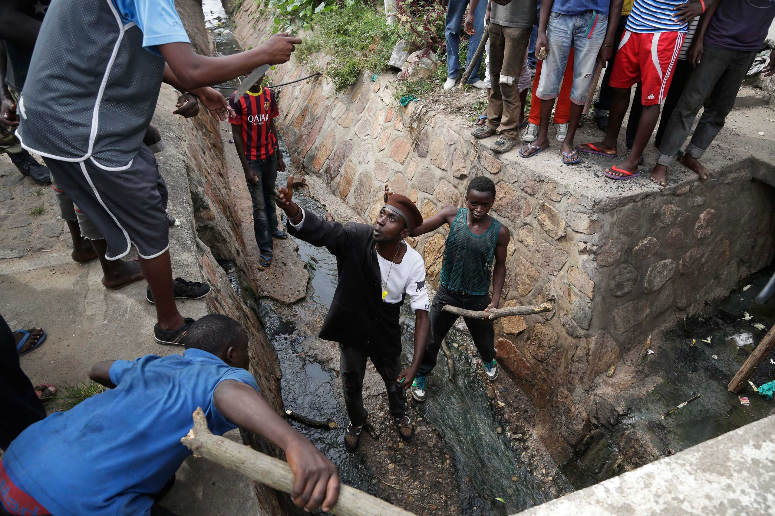 Demonstrators prepare to flush out Niyonzima, who escaped a lynching by running into a sewer.