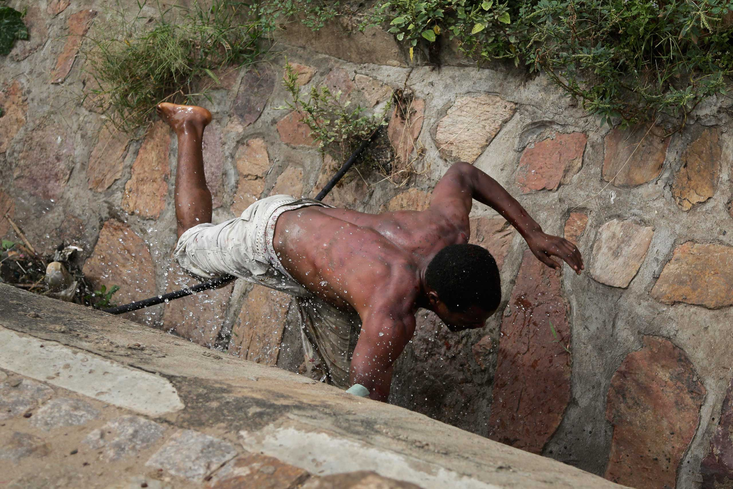 Niyonzima falls in the sewer as he flees from his house under a hail of stones thrown by a mob.