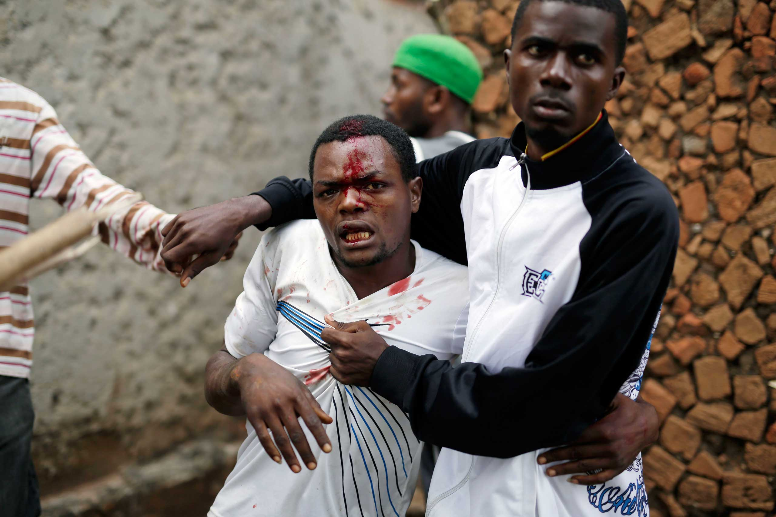 Jean Claude Niyonzima, a suspected member of the ruling party's Imbonerakure youth militia, is restrained as a mob gathers around his house, as protests continue against  President Pierre Nkurunziza's decision to seek a third term in office in the Cibitoke district of Bujumbura, Burundi on May 7, 2015.