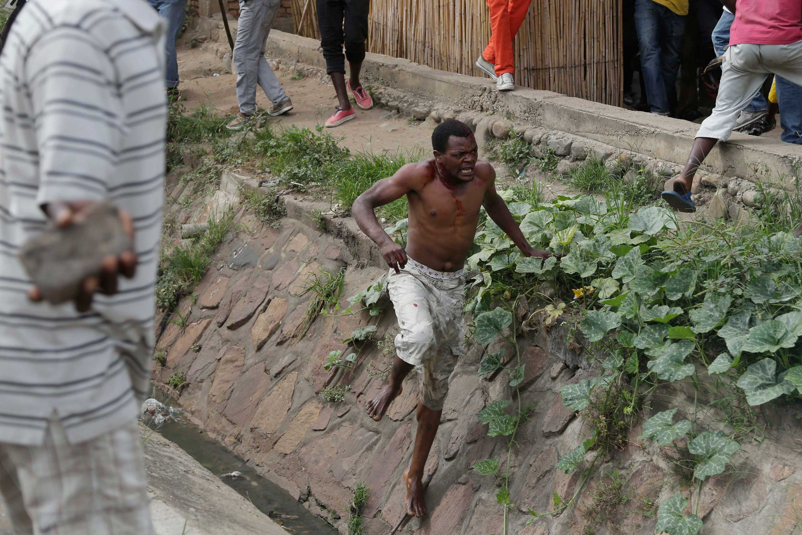 Niyonzima flees from his house into a sewer under a hail of stones thrown by a mob.