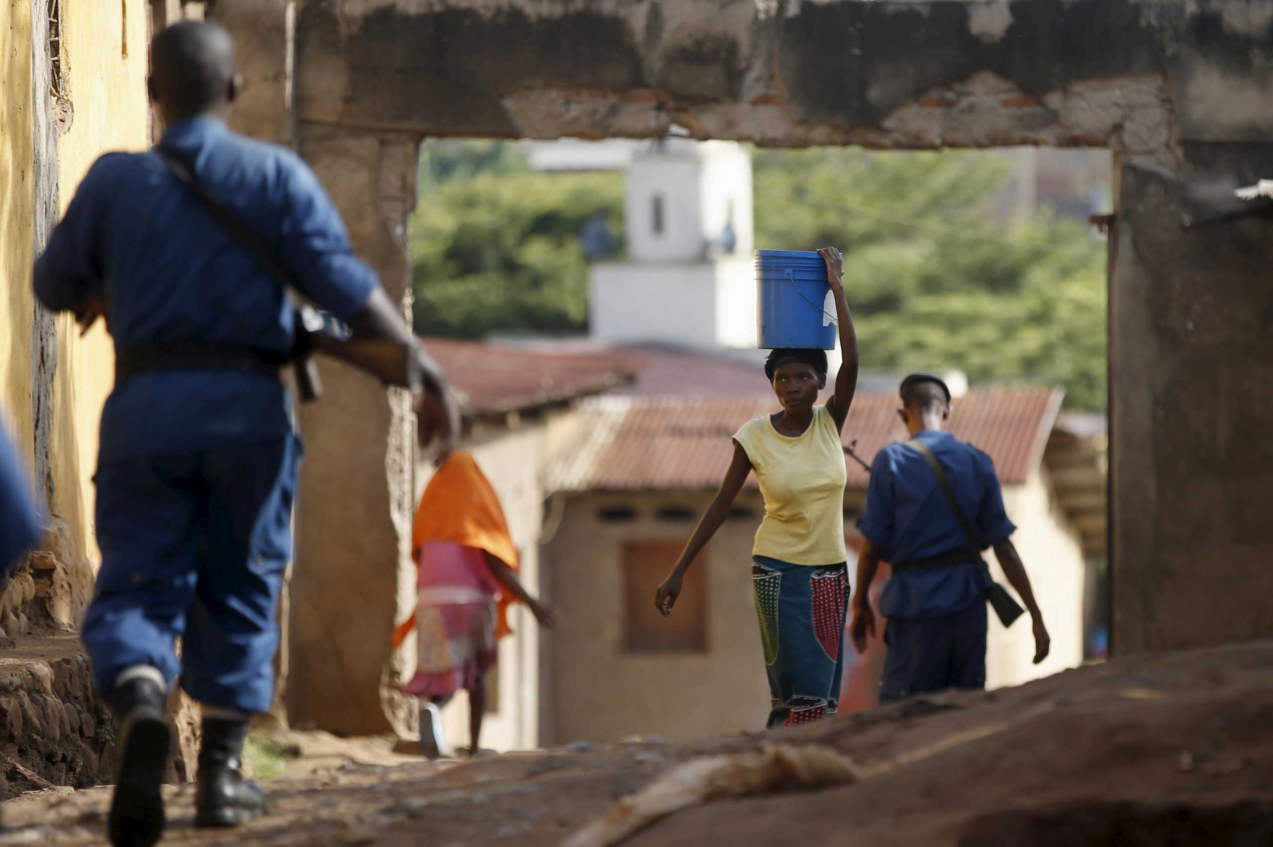 A woman passes by policemen in a street in Bujumbura, Burundi on May 15, 2015.