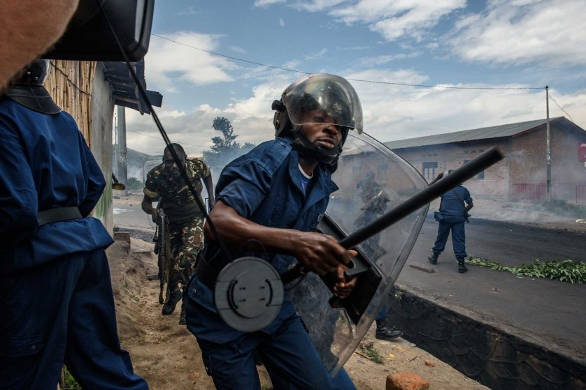 A police officer holding a baton and army forces run after protestors throwing stones during a demonstration against incumbent president Pierre Nkurunziza's bid for a third term in Bujumbura on May 13, 2015.