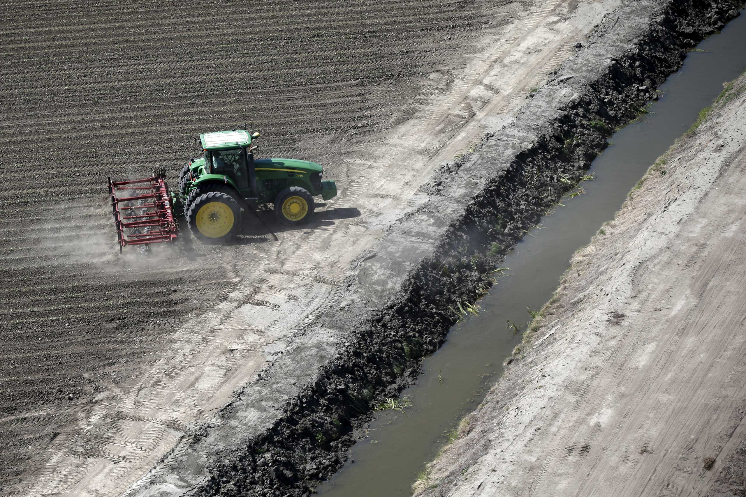 A tractor ploughs a field next to a canal in Los Banos, Calif. on May 5, 2015. California water regulators on Tuesday adopted the state's first rules for mandatory cutbacks in urban water use as the region's catastrophic drought enters its fourth year. However, the state's massive agricultural sector, which the Public Policy Institute of California says uses 80 percent of human-related consumption, has been exempted from cutbacks.