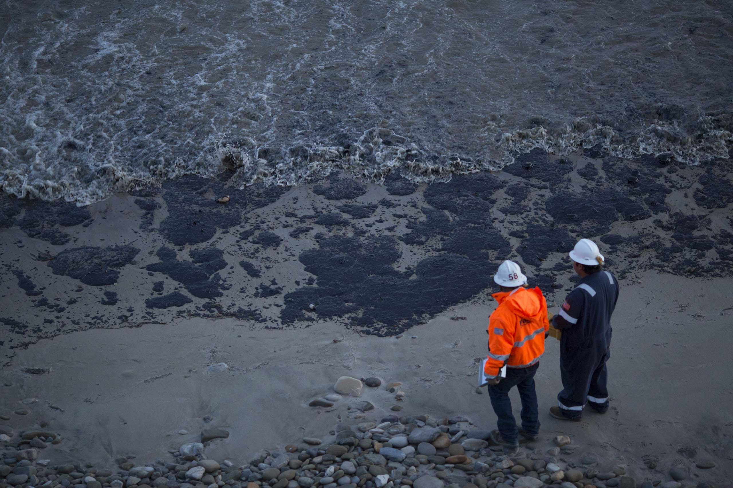 Officials walk along an the oil-covered beach in Goleta, Calif. on May 19, 2015.