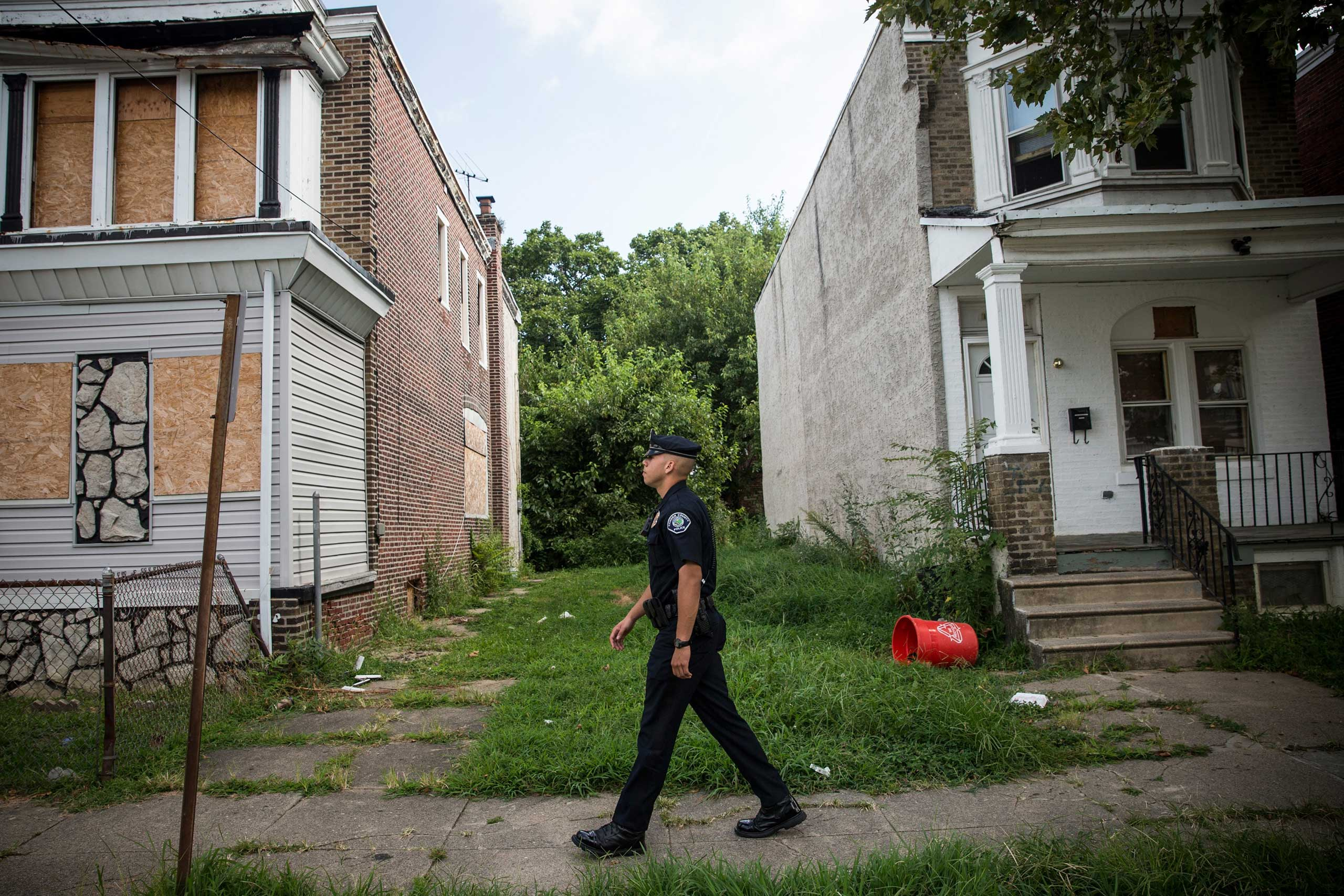 Officer Adam Fulmore, of the Camden County Police Department, goes on a foot patrol in the Parkside neighborhood of Camden, N.J. on Aug. 22, 2013.