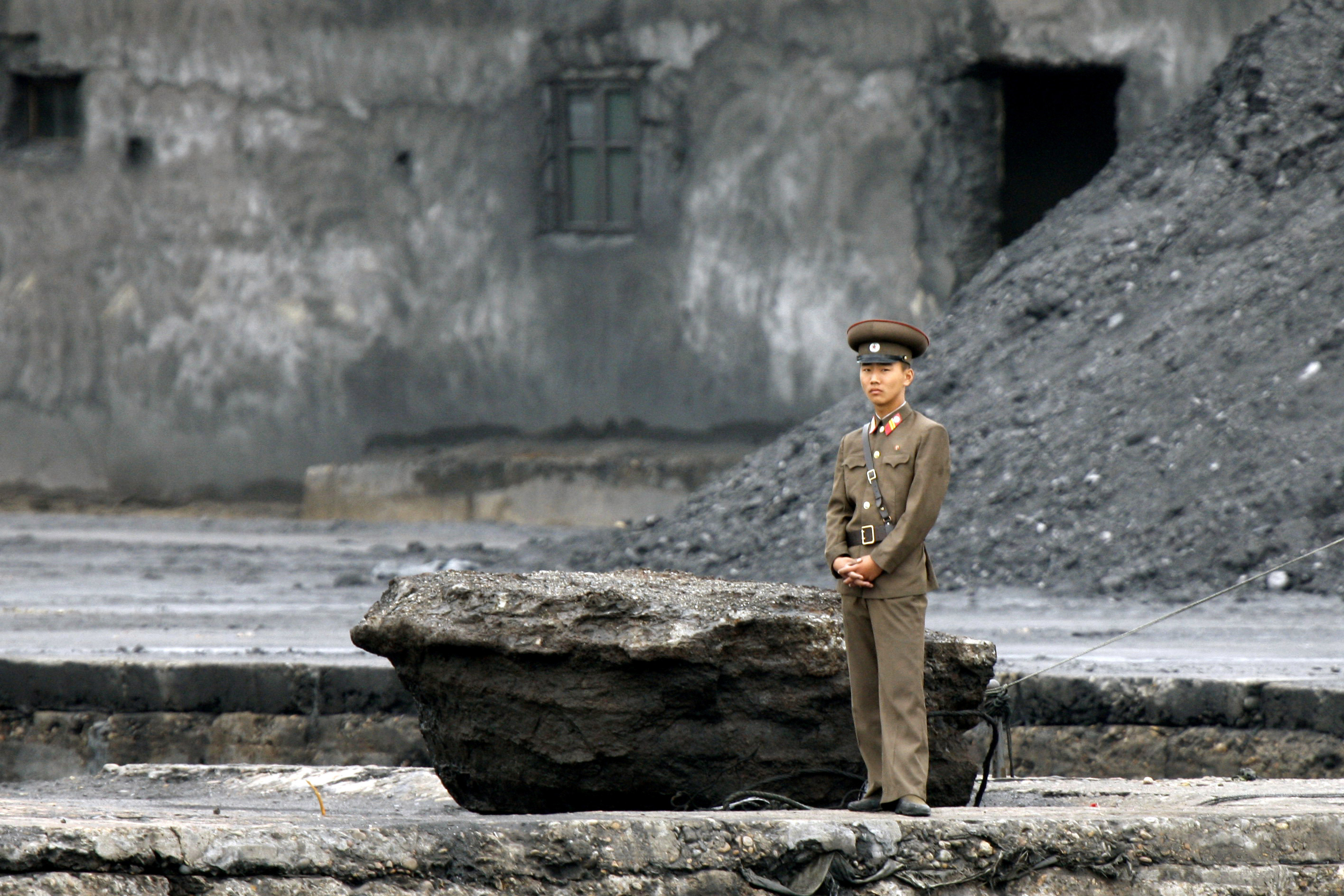 A North Korean soldier stands on the river bank in Sinuiju, North Korea, opposite the Chinese border city of Dandong, on June 12, 2013.