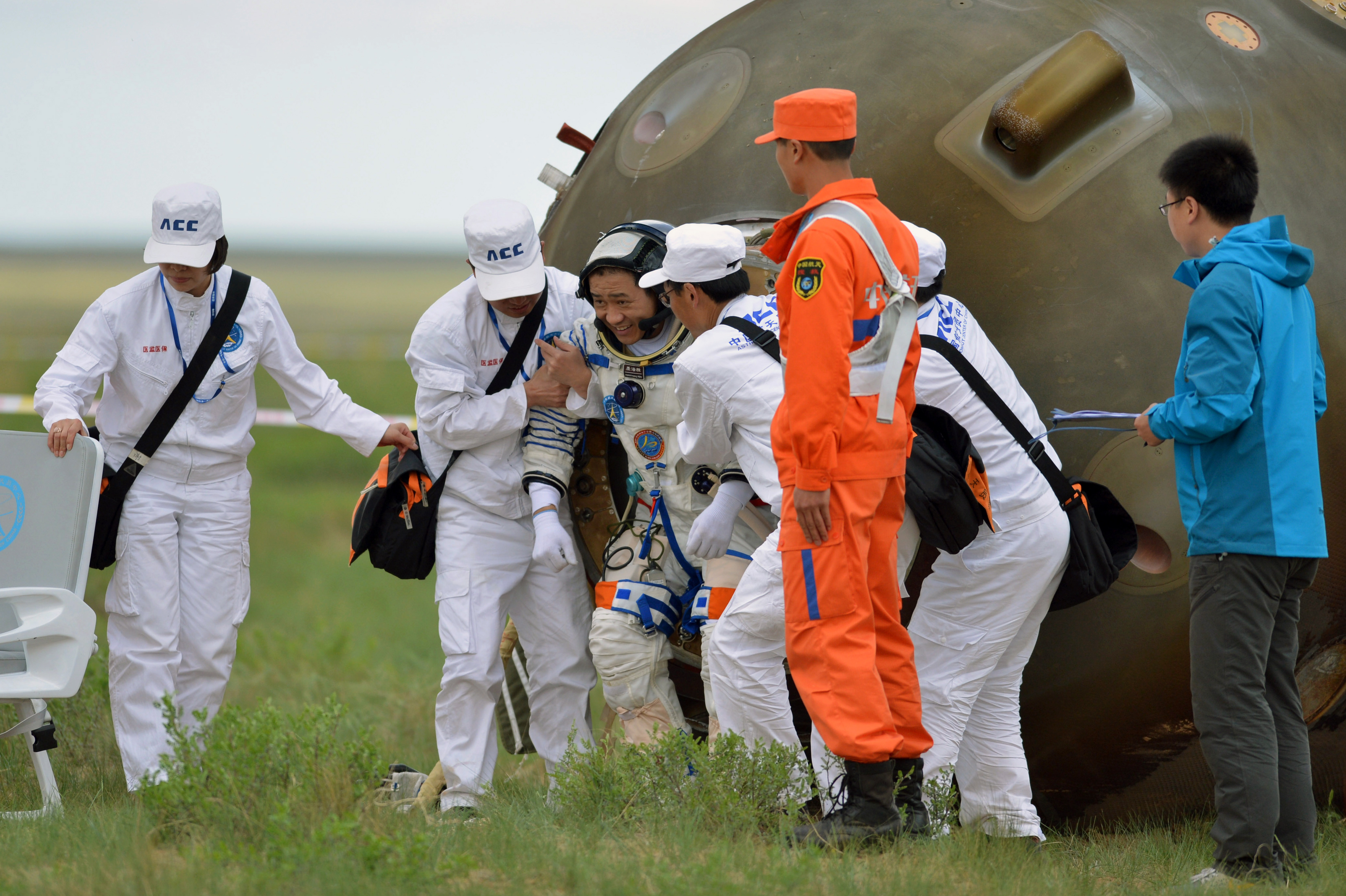 Welcome home: Nie Haisheng is helped out of his Shenzhou 10 spacecraft after a 15-day mission in 2013.