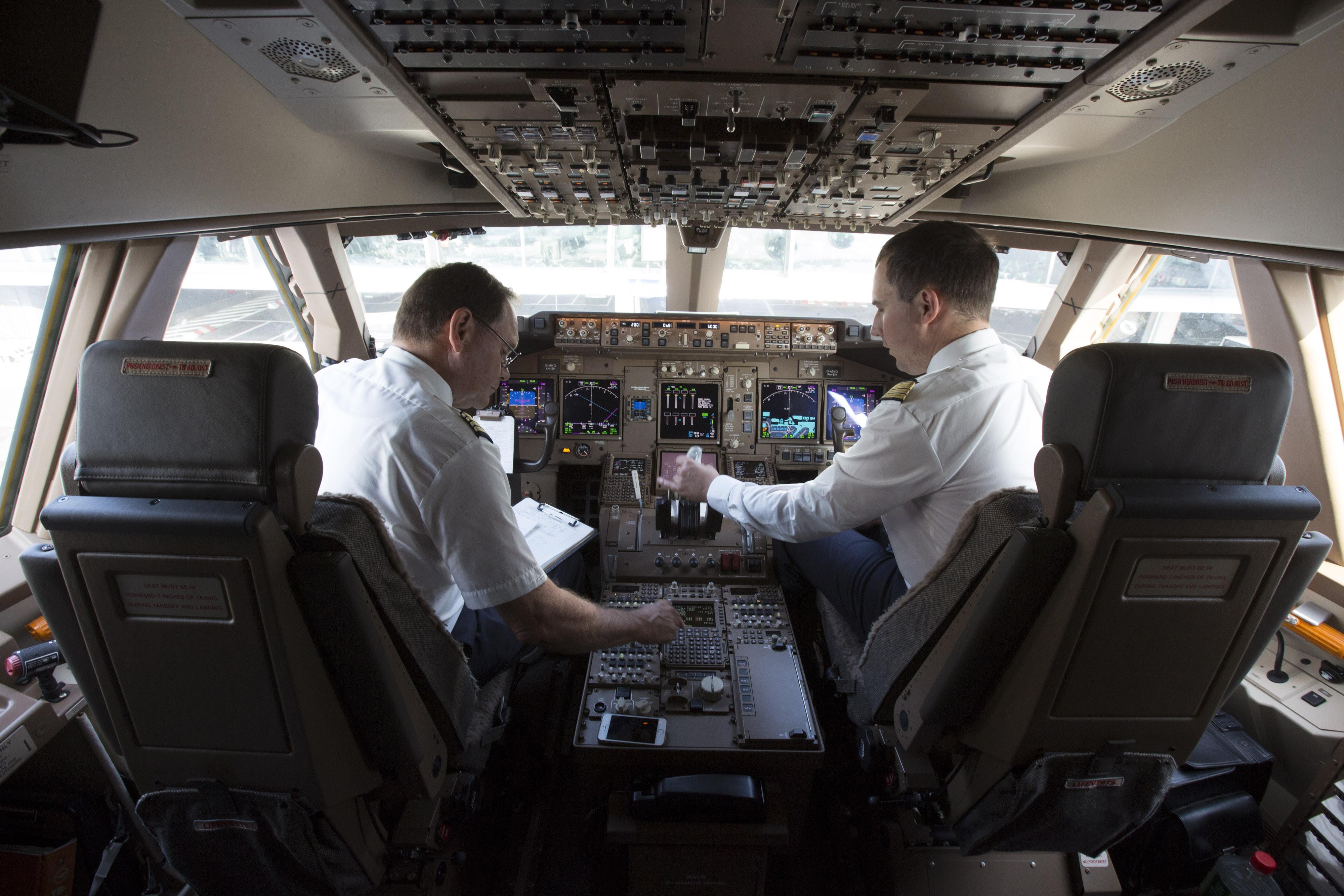 A Deutsche Lufthansa AG pilot, left, and co-pilot sit in the cockpit of a Boeing 747-8 passenger aircraft on Oct. 2, 2014.