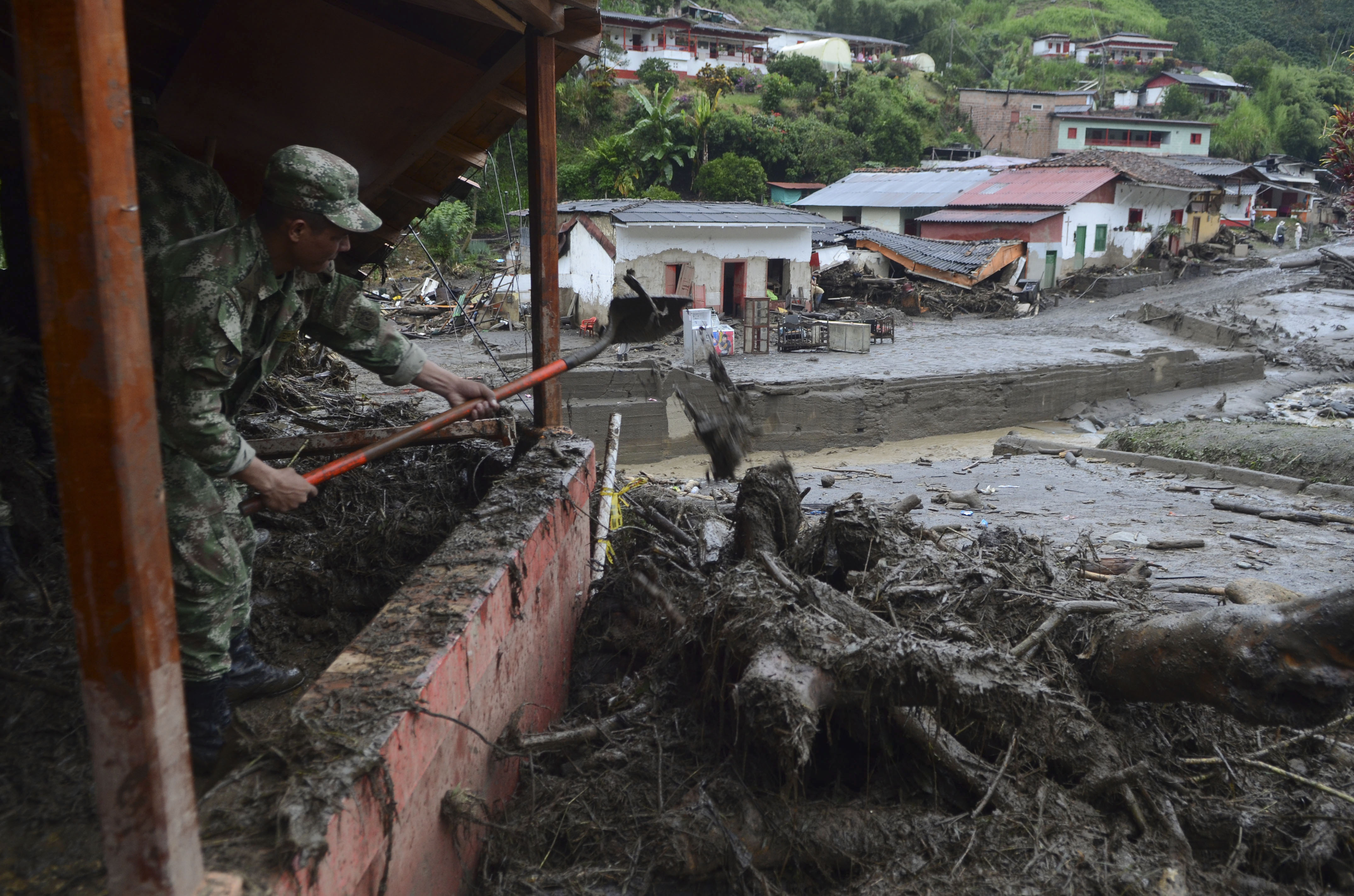 A soldier shovels mud from a house damaged by a mudslide in Salgar, in Colombia's northwestern state of Antioquia, May 19, 2015.