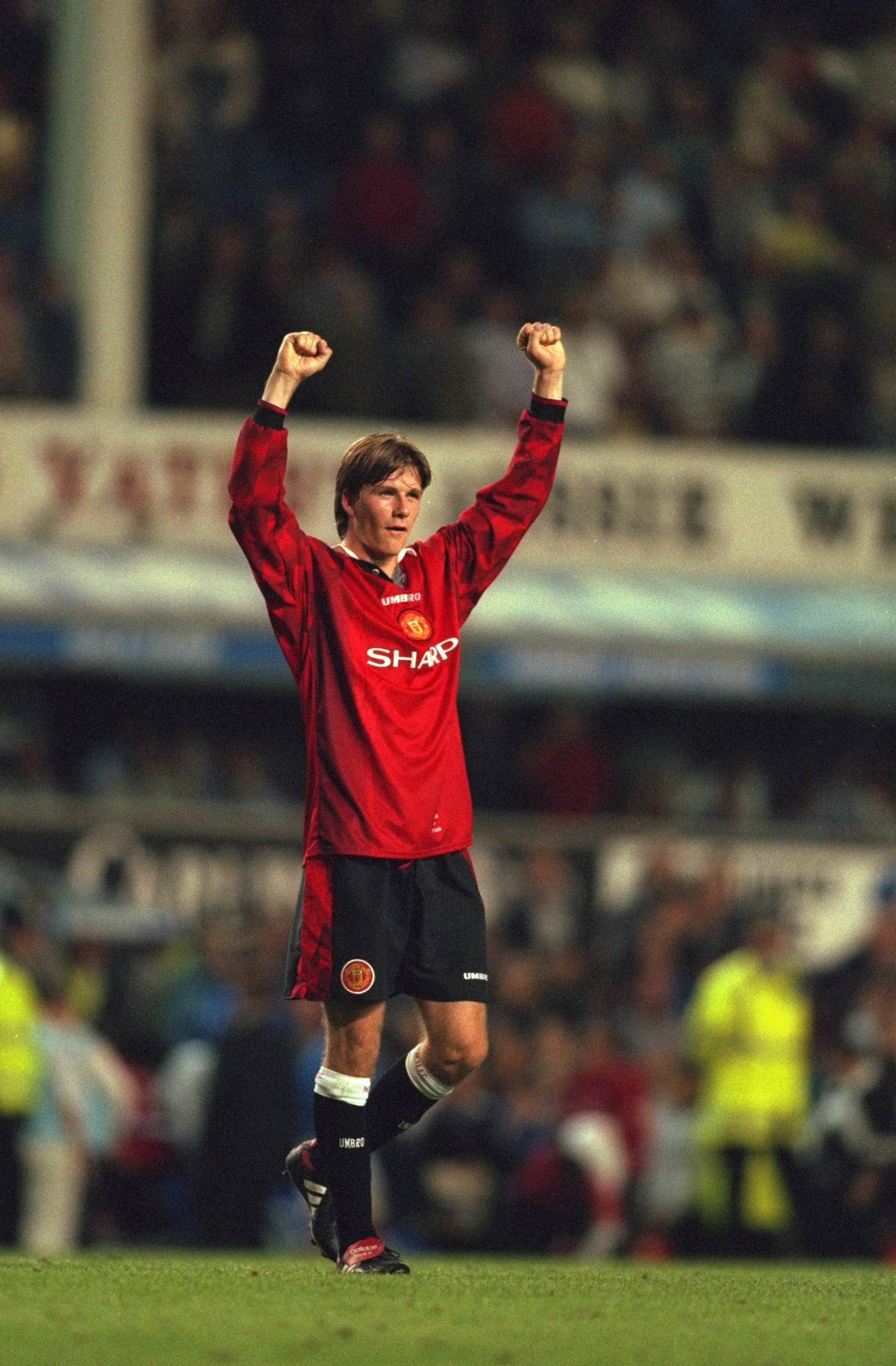 David Beckham of Manchester United celebrates to the crowd after scoring a goal during the FA Carling Premiership match against Everton played at Goodison Park in Liverpool, England in 1997.