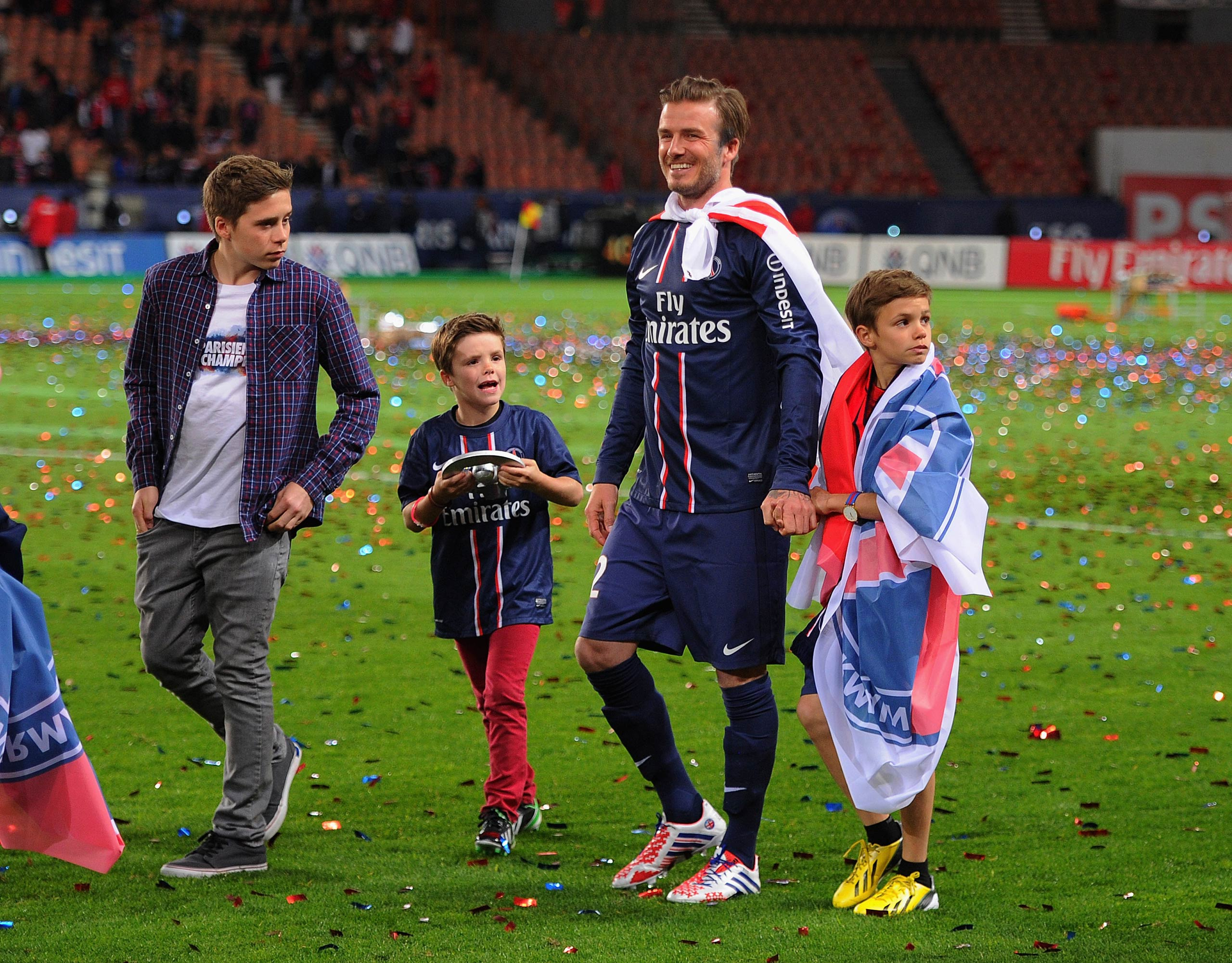 David Beckham waves to the crowd with his sons, Brooklyn, Romeo and Cruz during his final soccer game, a French L1 soccer match between Paris St. Germain and Brest at Parc des Princes stadium in Paris in 2013.