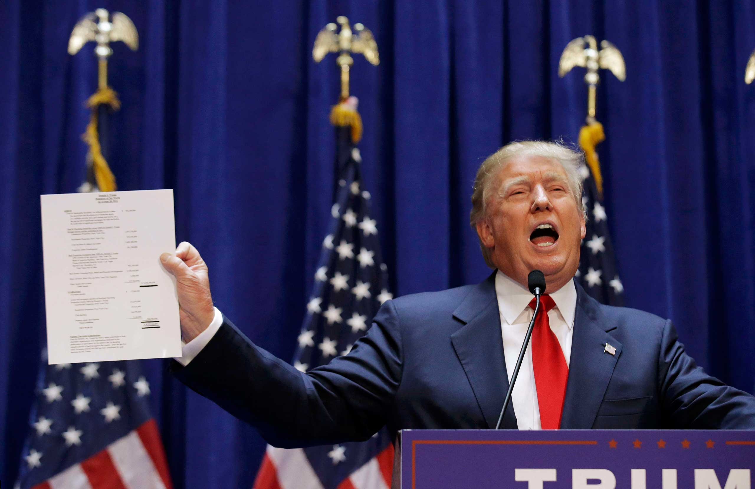 Donald Trump holds up his financial statement showing his net worth as he formally announces his campaign for the 2016 Republican presidential nomination during an event at Trump Tower in New York City on June 16, 2015.