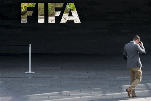 A man walks next to the FIFA logo at the FIFA headquarters in Zurich, on May 27, 2015.