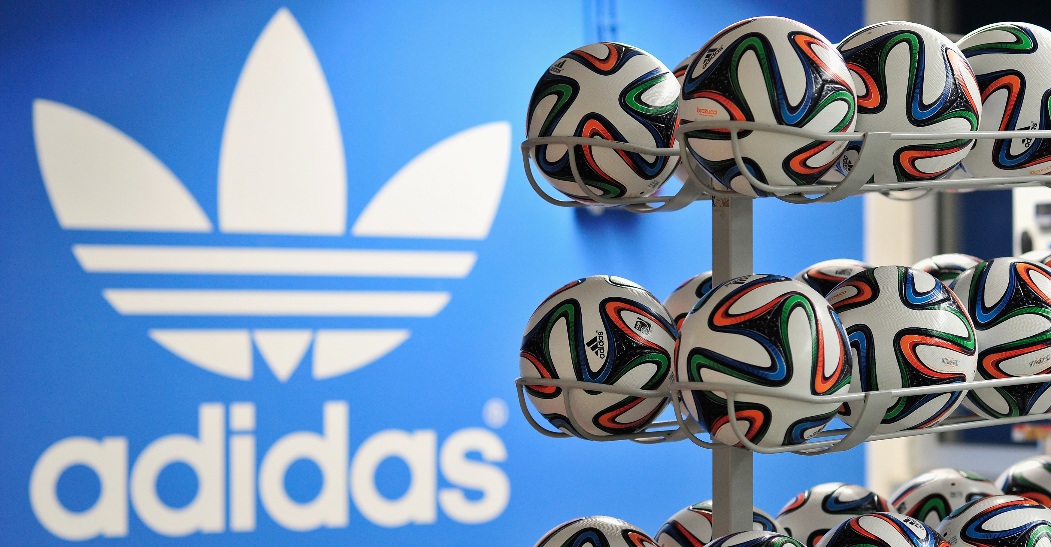 Brazuca match balls for the FIFA World Cup 2014 lie in a rack in front of the adidas logo on December 6, 2013 in Scheinfeld near Herzogenaurach, Germany.