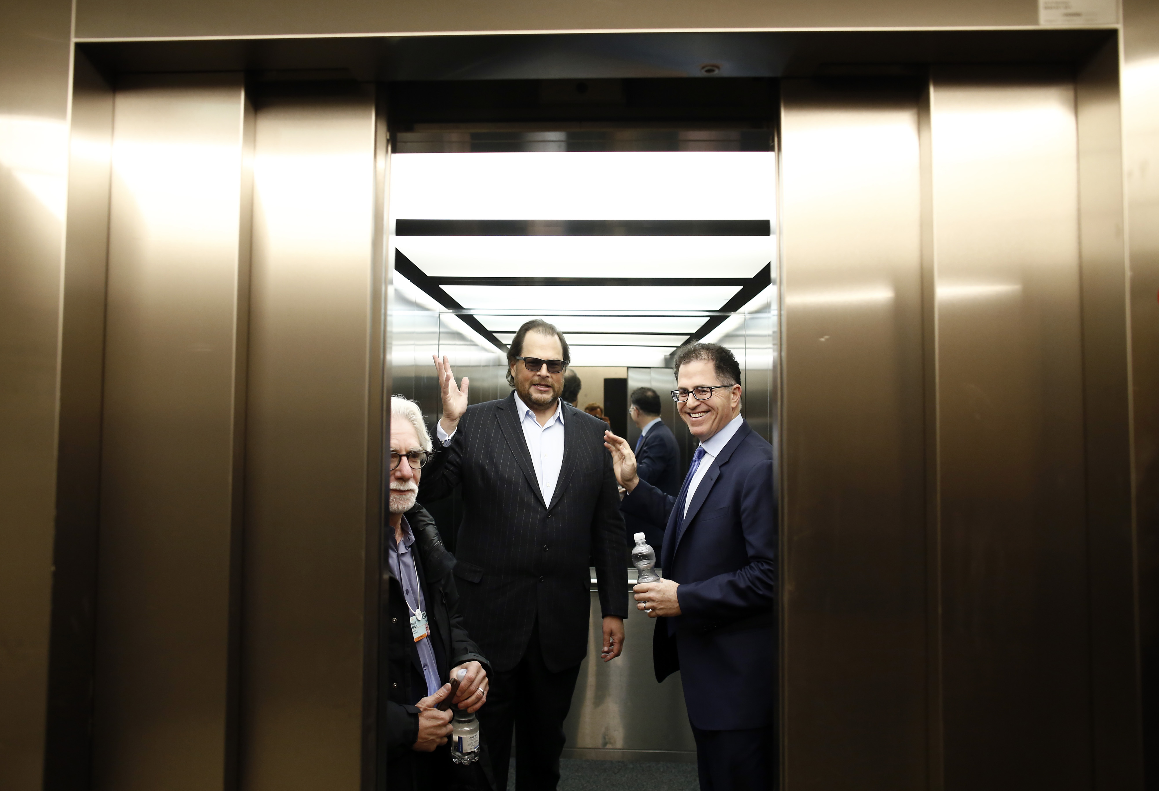 Marc Benioff, chairman and chief executive officer of Salesforce.com Inc., center, and Michael Dell, chairman and chief executive officer of Dell Inc., right, wave from inside an elevator following a Bloomberg Television interview on day two of the World Economic Forum (WEF) in Davos, Switzerland, on Jan. 22, 2015.