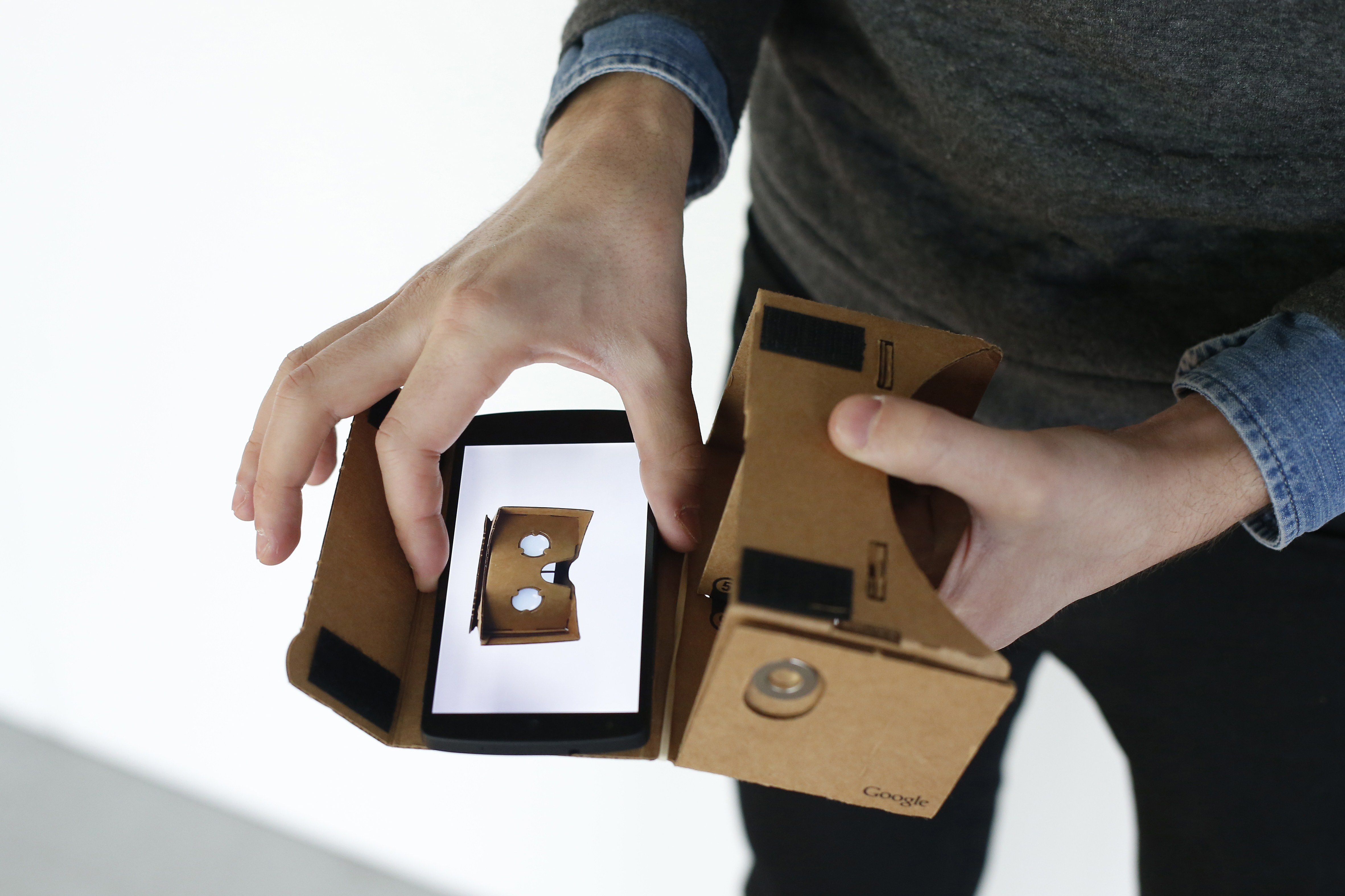 A Google employee presents a Google Cardboard virtual reality headset for android smartphones during a Google promotion event at the City of Fashion and Design (Cite de la mode et du design) in Paris on November 4, 2014.