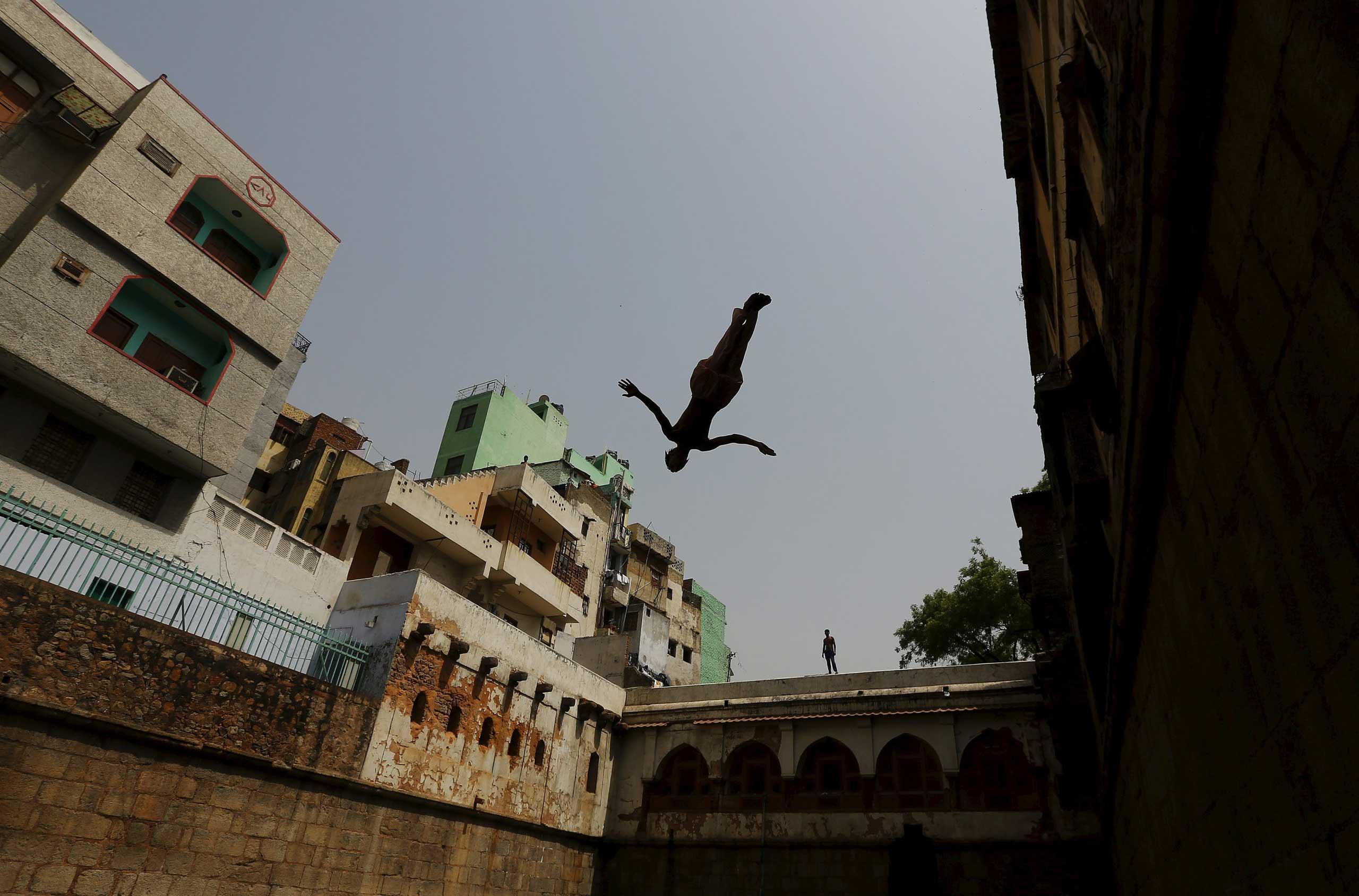 A boy jumps into a step well built inside the shrine of Sufi Saint Nizamuddin Auliya in New Delhi on May 24, 2015.