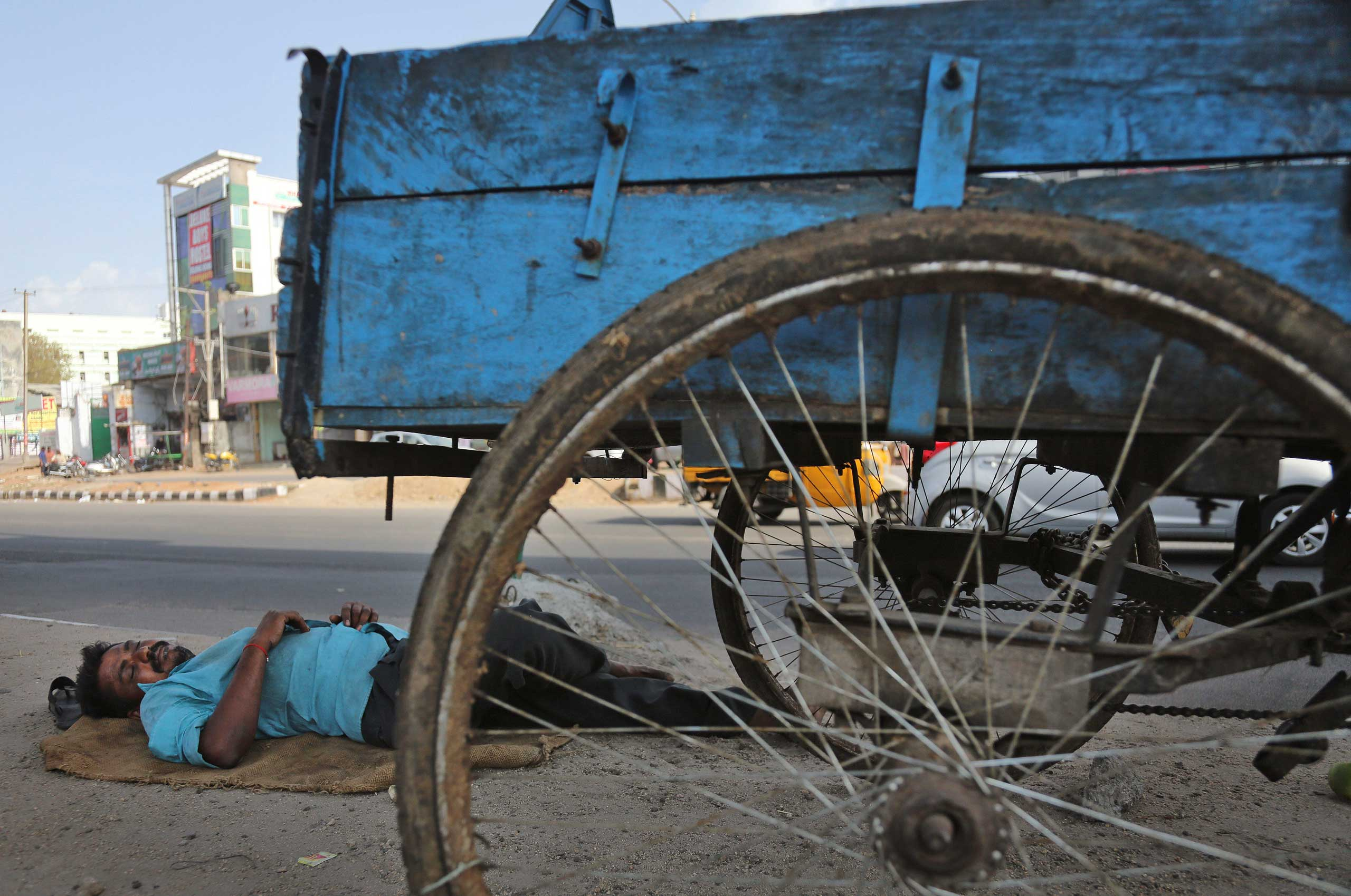 A rickshaw puller rests under the shade of an overhead bridge on a hot summer day in Hyderabad, India on May 25, 2015.