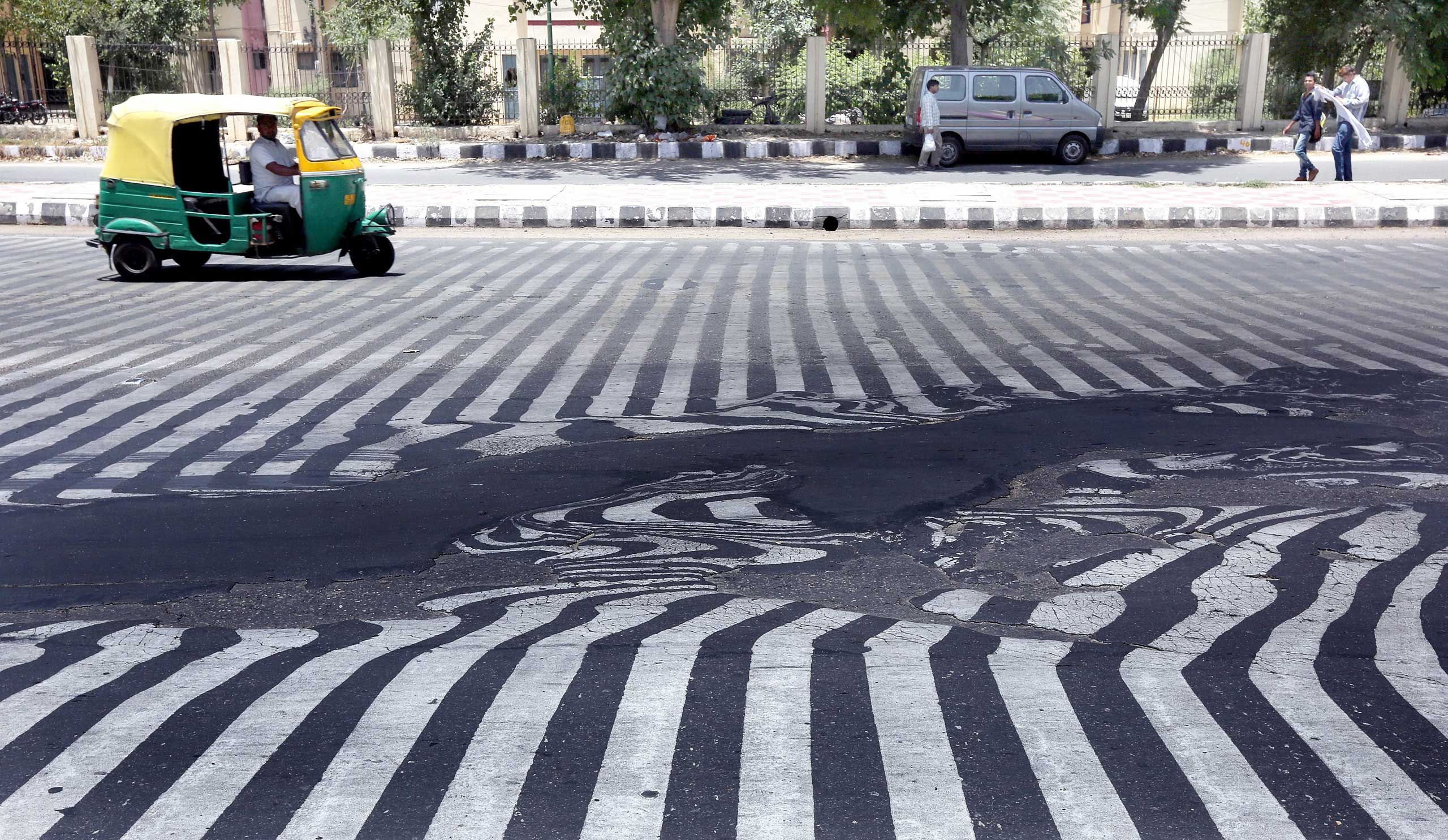 Road markings appear distorted as the asphalt starts to melt due to the high temperature in New Delhi on May 27, 2015.