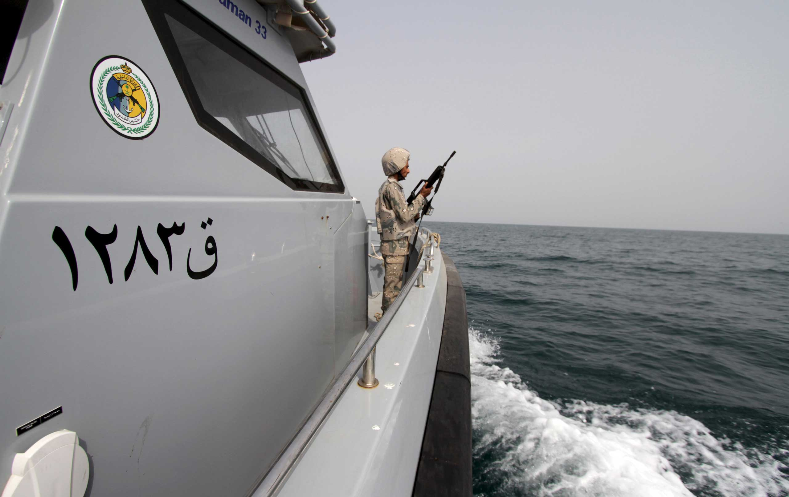 A Saudi border guard watches as he stands in a boat off the coast of the Red Sea on Saudi Arabia's maritime border with Yemen, near Jizan April 8, 2015.