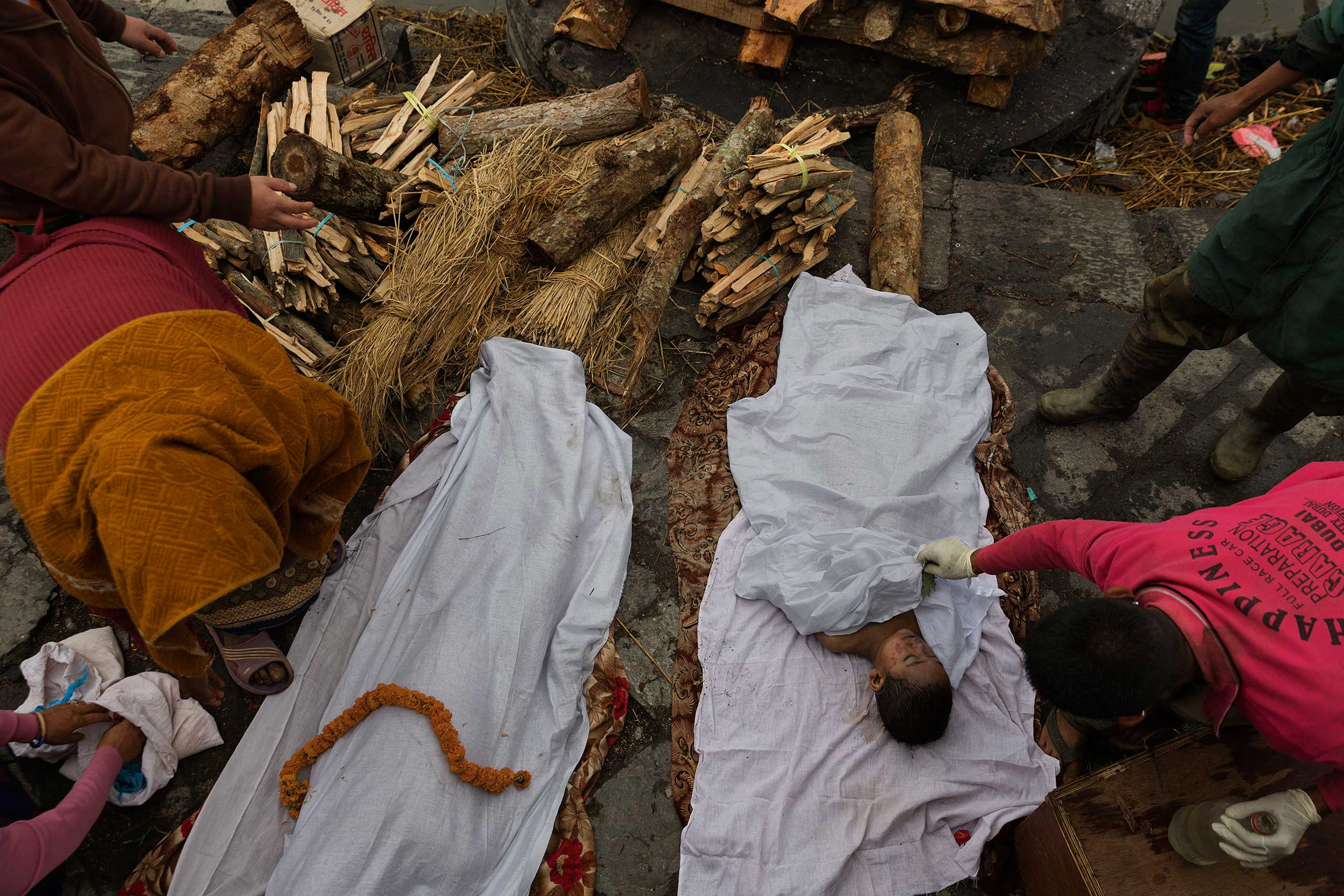 Bodies are prepared for cremation during a Hindu ritual at the Pashupatinath Temple in Kathmandu on April 28, 2015, three days after a 7.8 magnitude earthquake devastated Nepal, killing at least 7,000 people and causing untold damage.