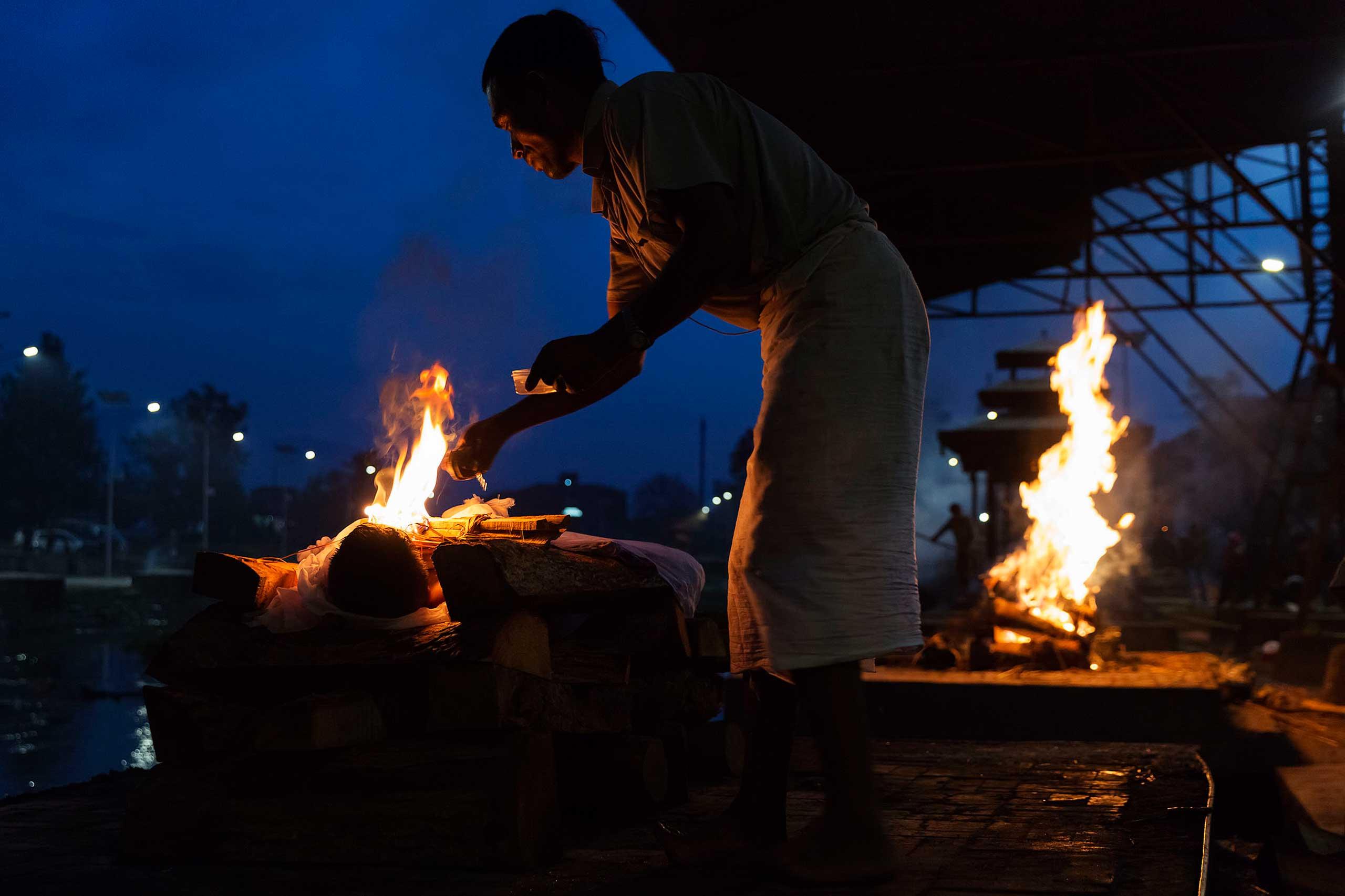 A man performs a Hindu cremation ritual at the Pashupatinath Temple in Kathmandu, April 28, 2015.