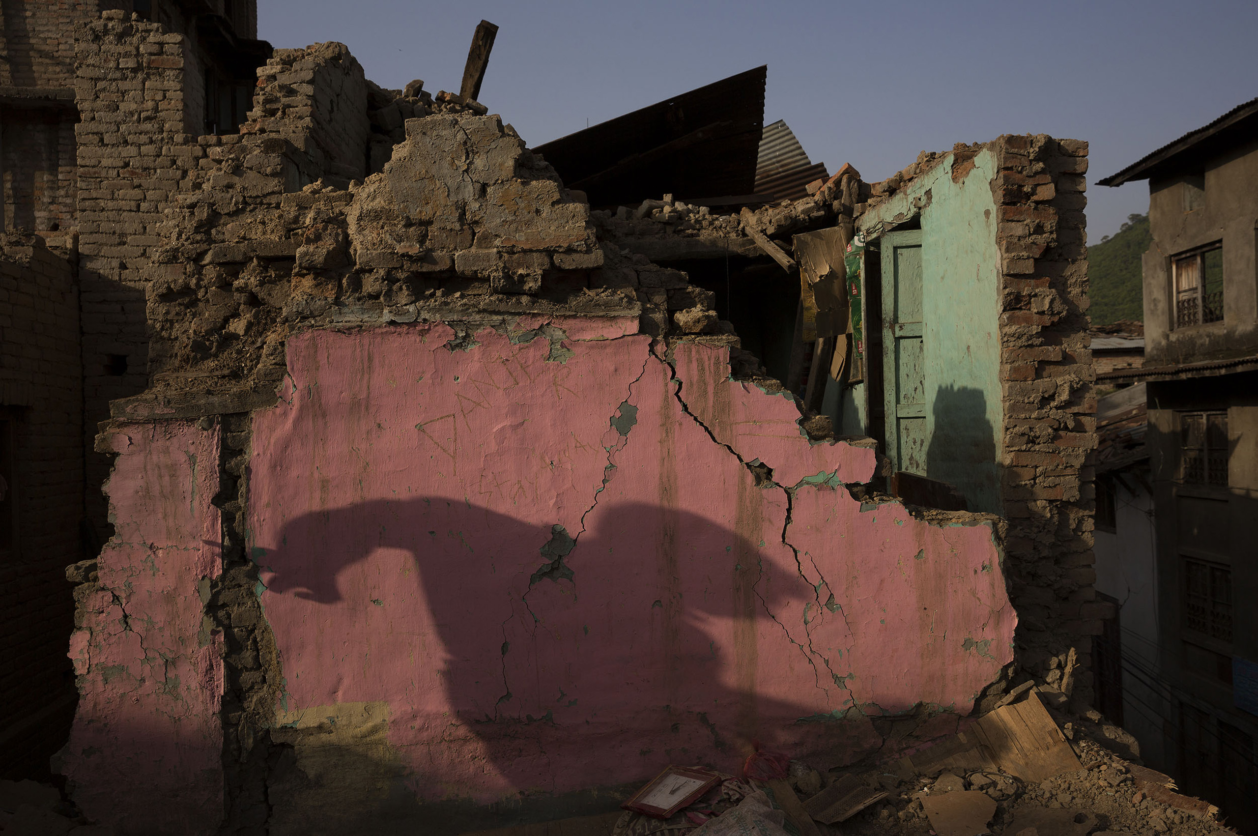 A shadow is reflected on the remains of a  collapsed house in the largely destroyed village of Sankhu on the outskirts of Katmandu, May 1, 2015.