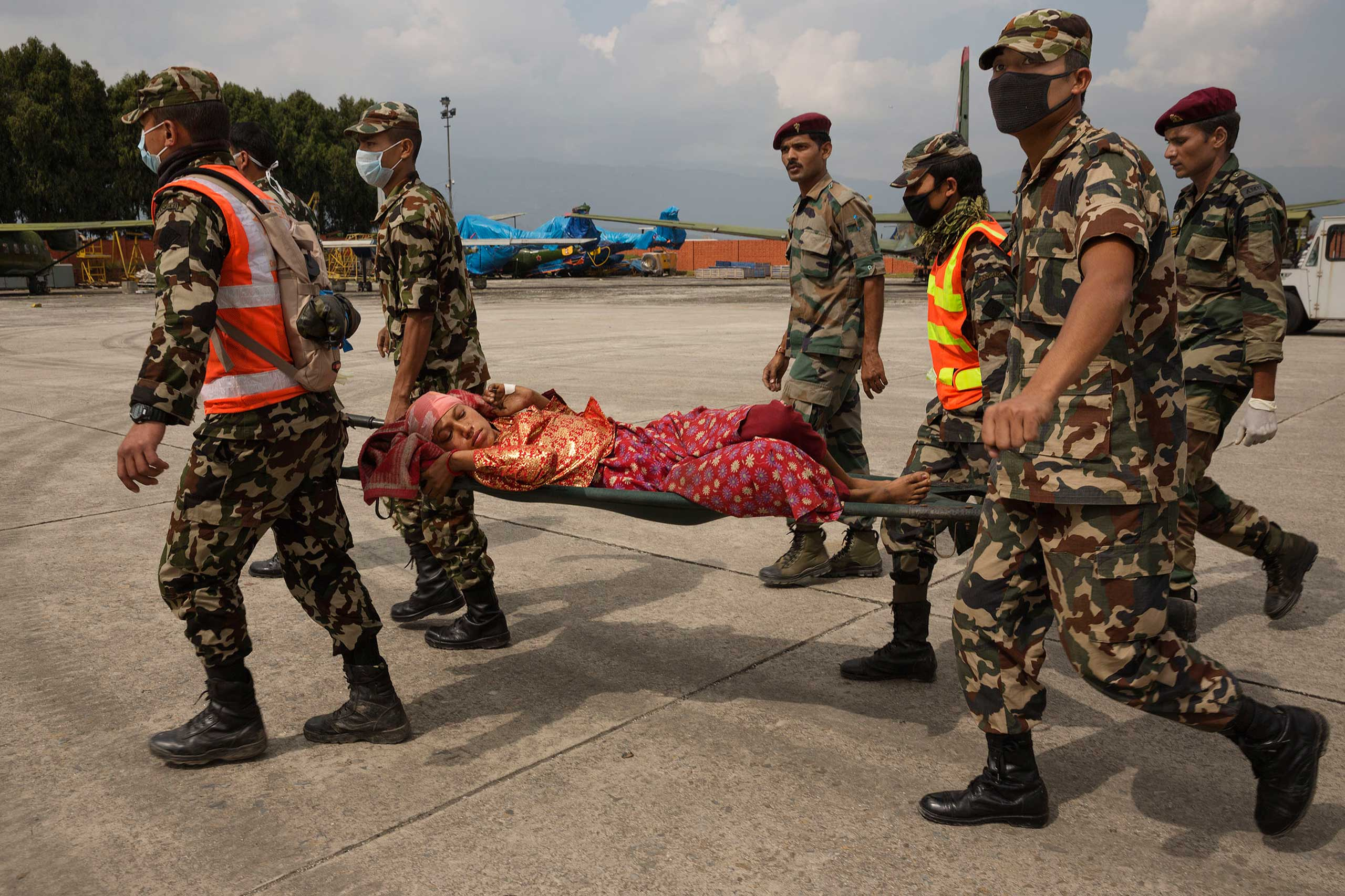 After being airlifted from a remote village to Kathmandu, an injured woman is carried to receive care, April 30, 2015.