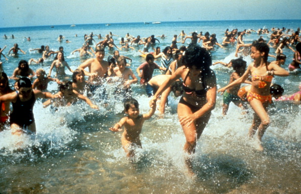 Crowds run out of the water in a scene from the film 'Jaws', 1975.
