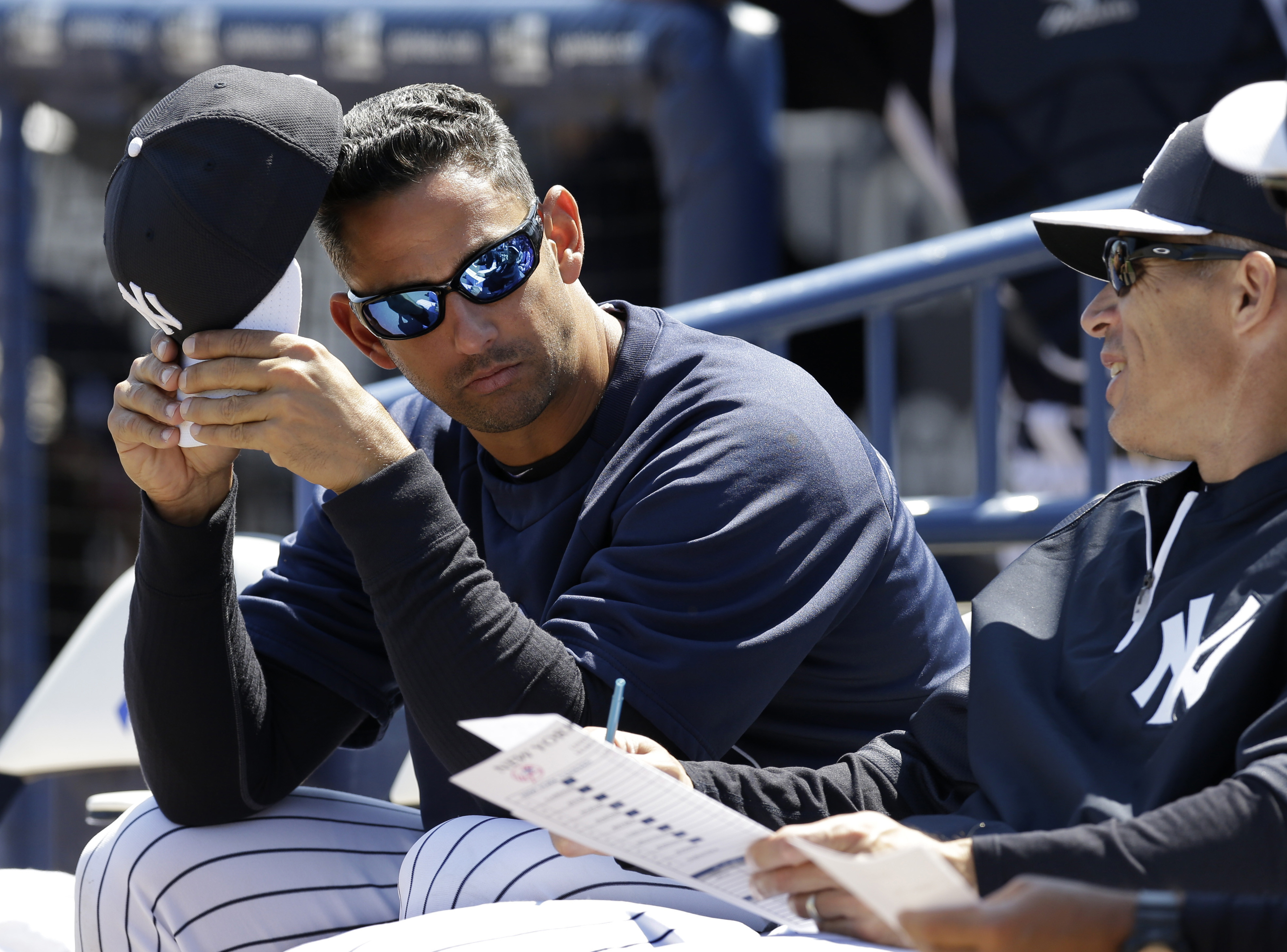 Former New York Yankees catcher Jorge Posada, left, in camp as a guest instructor, sits with New York Yankees manager Joe Girardi before a spring training baseball game against the Miami Marlins in Tampa, on March 15, 2013.