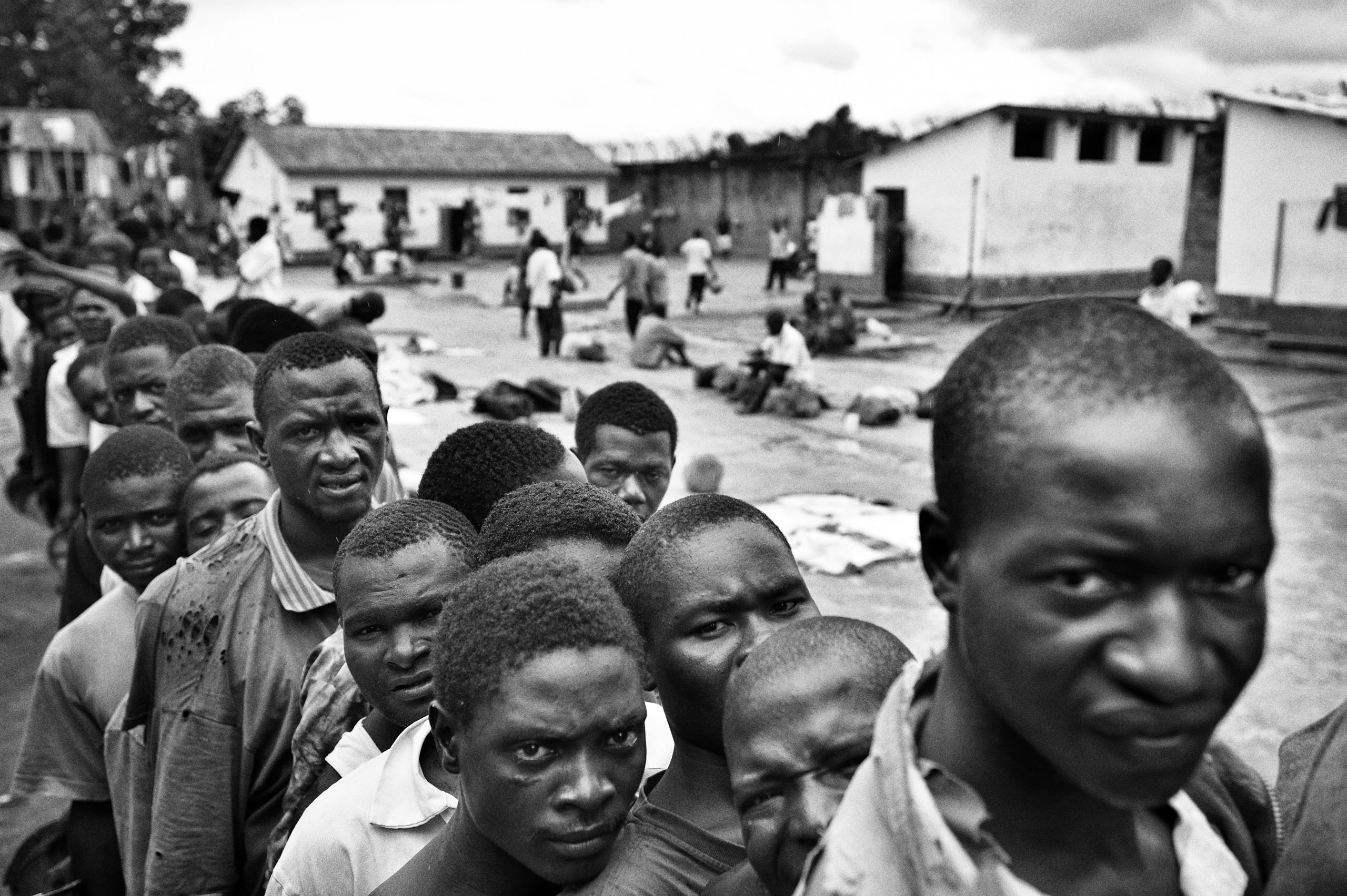 Inmates wait in line to receive food once a day in Mzuzu, Malawi.
