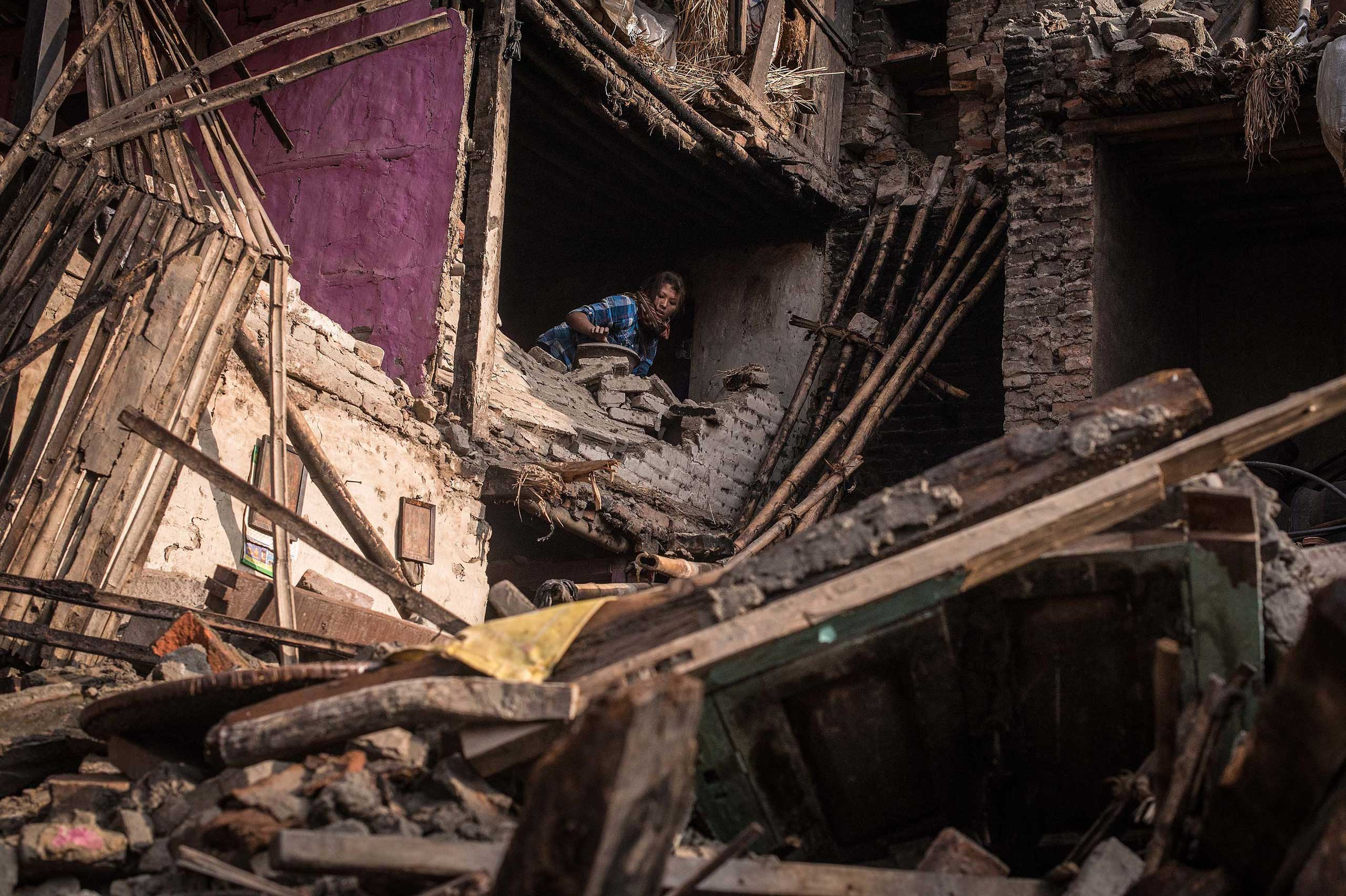 A victim of the earthquake searches for her belongings among debris of her house on in Bhaktapur, Nepal on April 29, 2015.