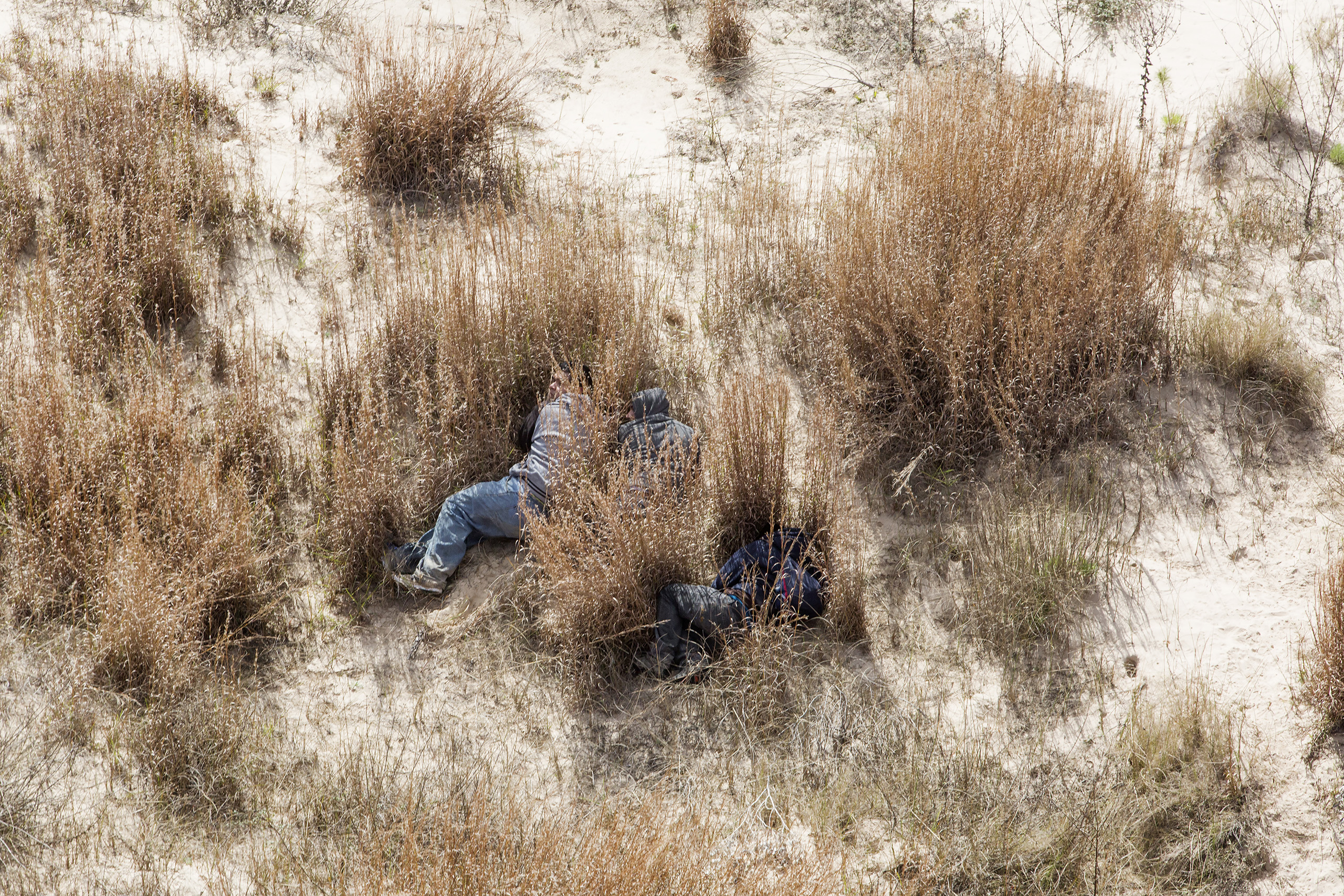 TIME LightBox: 'The Corridor of Death': Along America's Second BorderMigrants hide on the edge of sand dunes as they are surrounded by Border Patrol Agents. These migrants were avoiding the interior checkpoint located in Sarita, Texas, on Rt. 77 North to San Antonio, Feb. 2015.