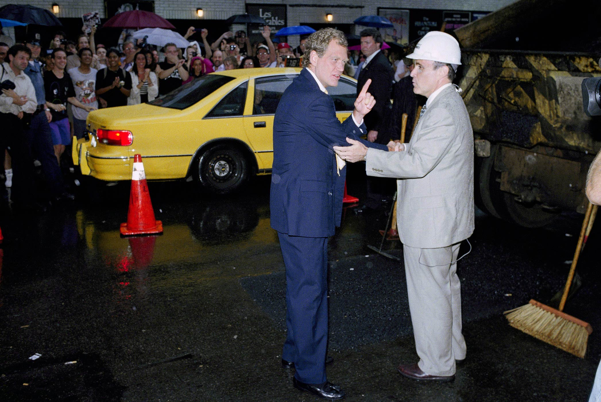 David Letterman greets New York City Mayor Rudolph Giuliani as he helps fill a large pothole on 53rd Street outside the Ed Sullivan Theater during a taping of the Late Show With David Letterman on July 26, 1994 in New York.