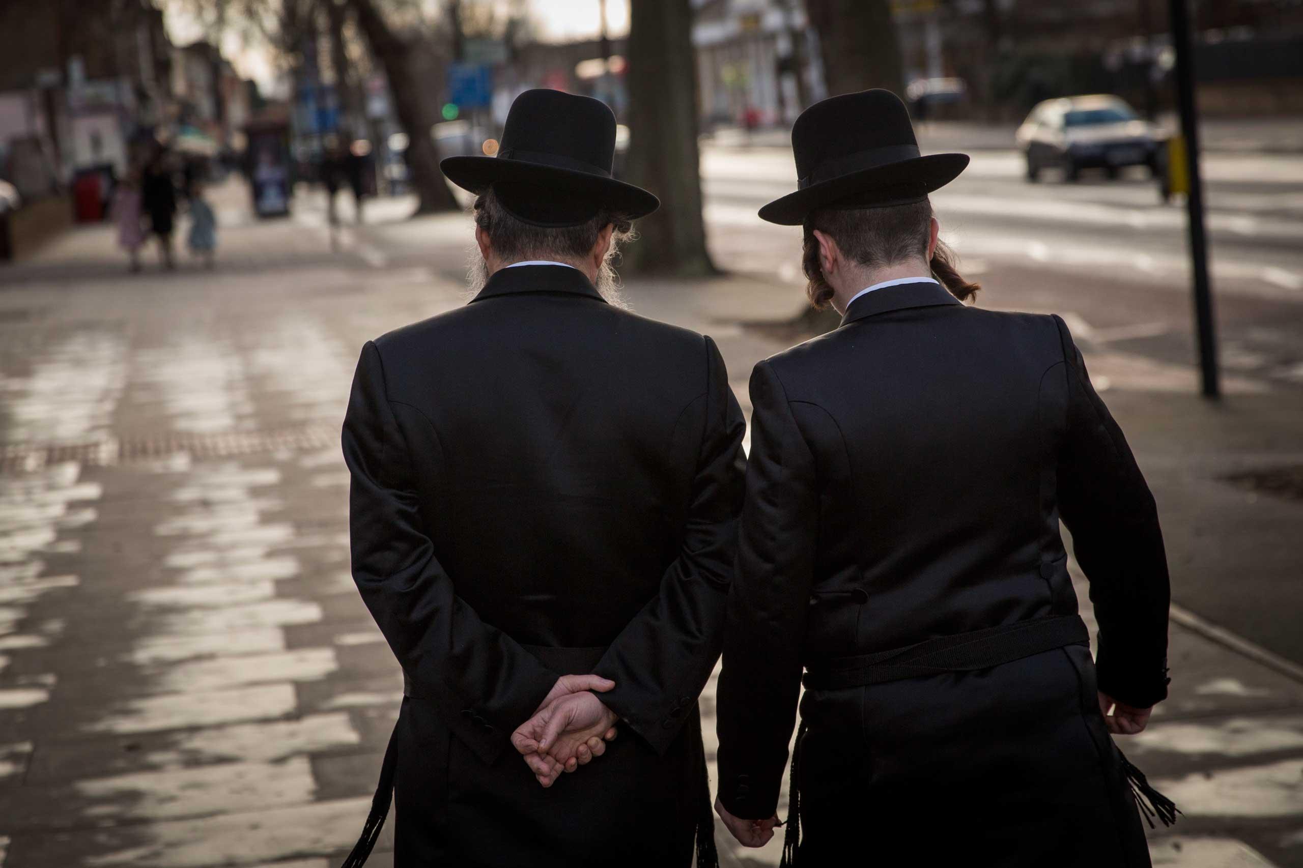 Ultra-orthodox Jewish men walk along the street in the Stamford Hill area of London on Jan. 17, 2015.