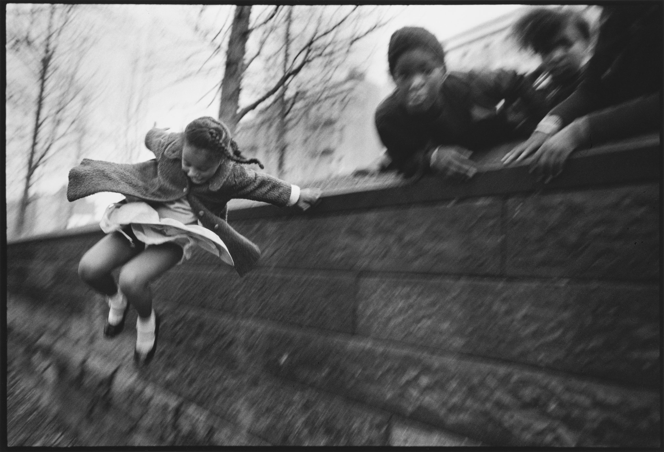 Girl jumping over a wall in Central Park. New York, 1967.