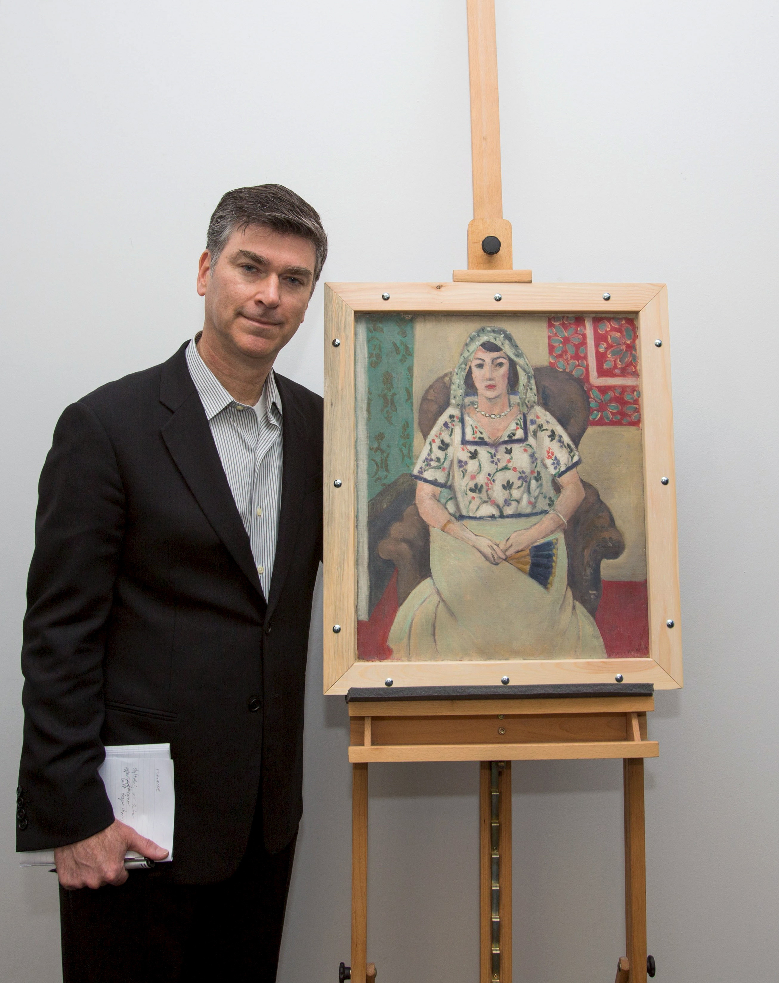 A handout picture provided by Wolf Heider-Sawall Art Recovery Group shows the representative of the Rosenberg family, Christopher Marinello, with the painting 'Seated Woman' by Henri Matisse on behalf of the family in Munich on May 15, 2015.