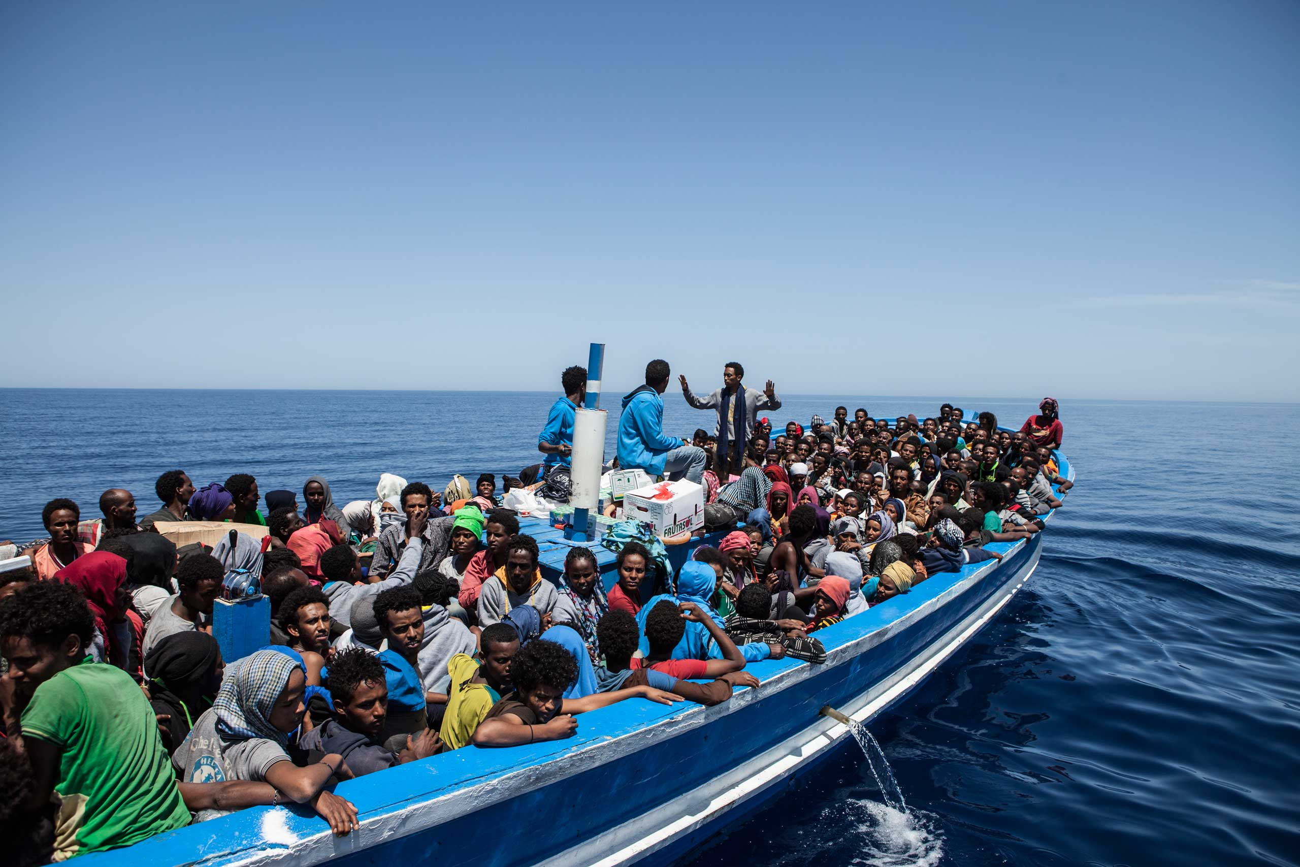 Migrants on a packed wooden boat wait to be rescued off the coast of Malta on May 3, 2015.