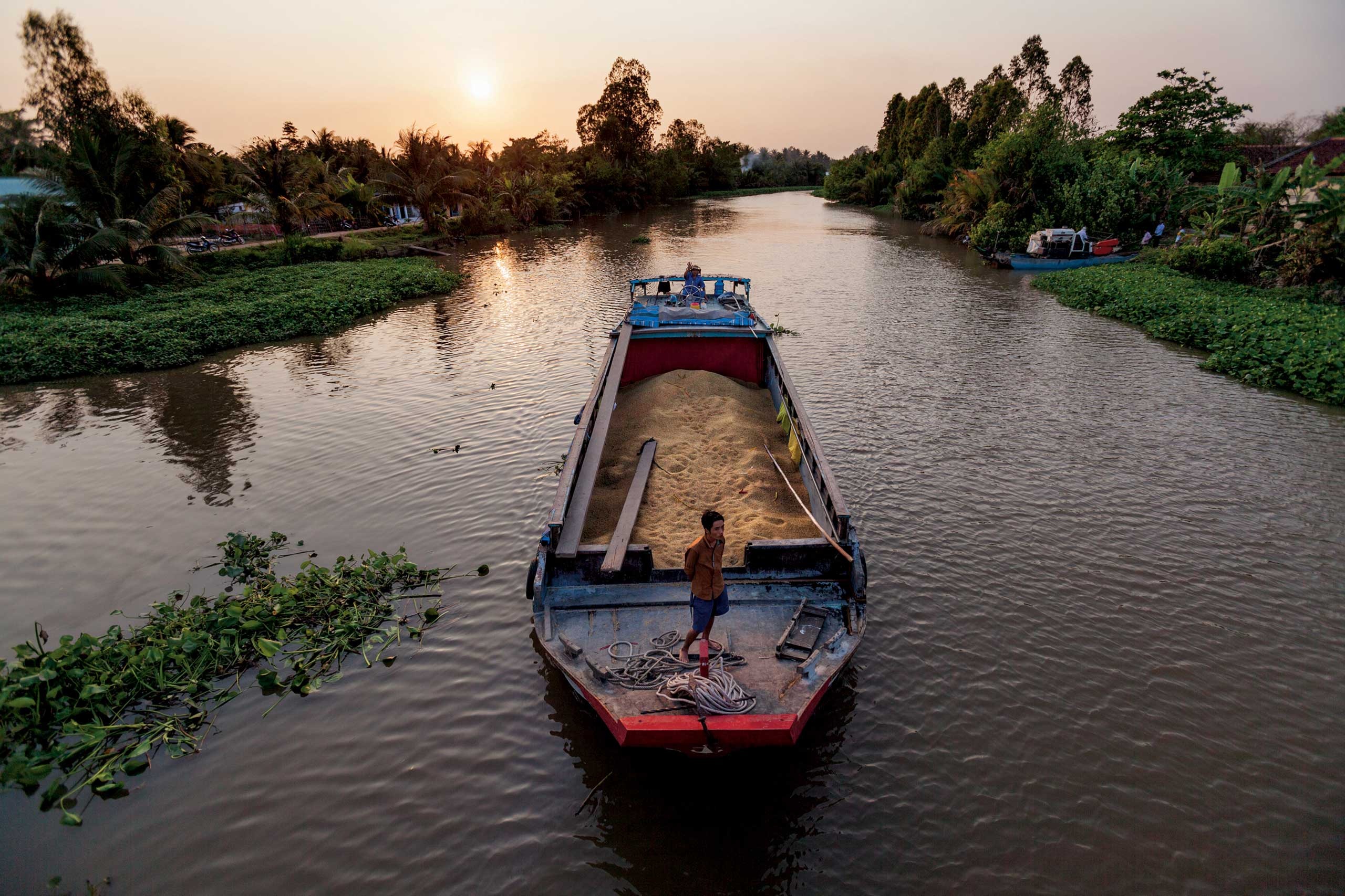From the May issue of National Geographic magazine: Harnessing the Mekong                               Vietnam                               A riverboat loaded with rice moves slowly through one of the canals that crisscross the delta. Dams will trap fertile sediments upstream, threatening harvests.