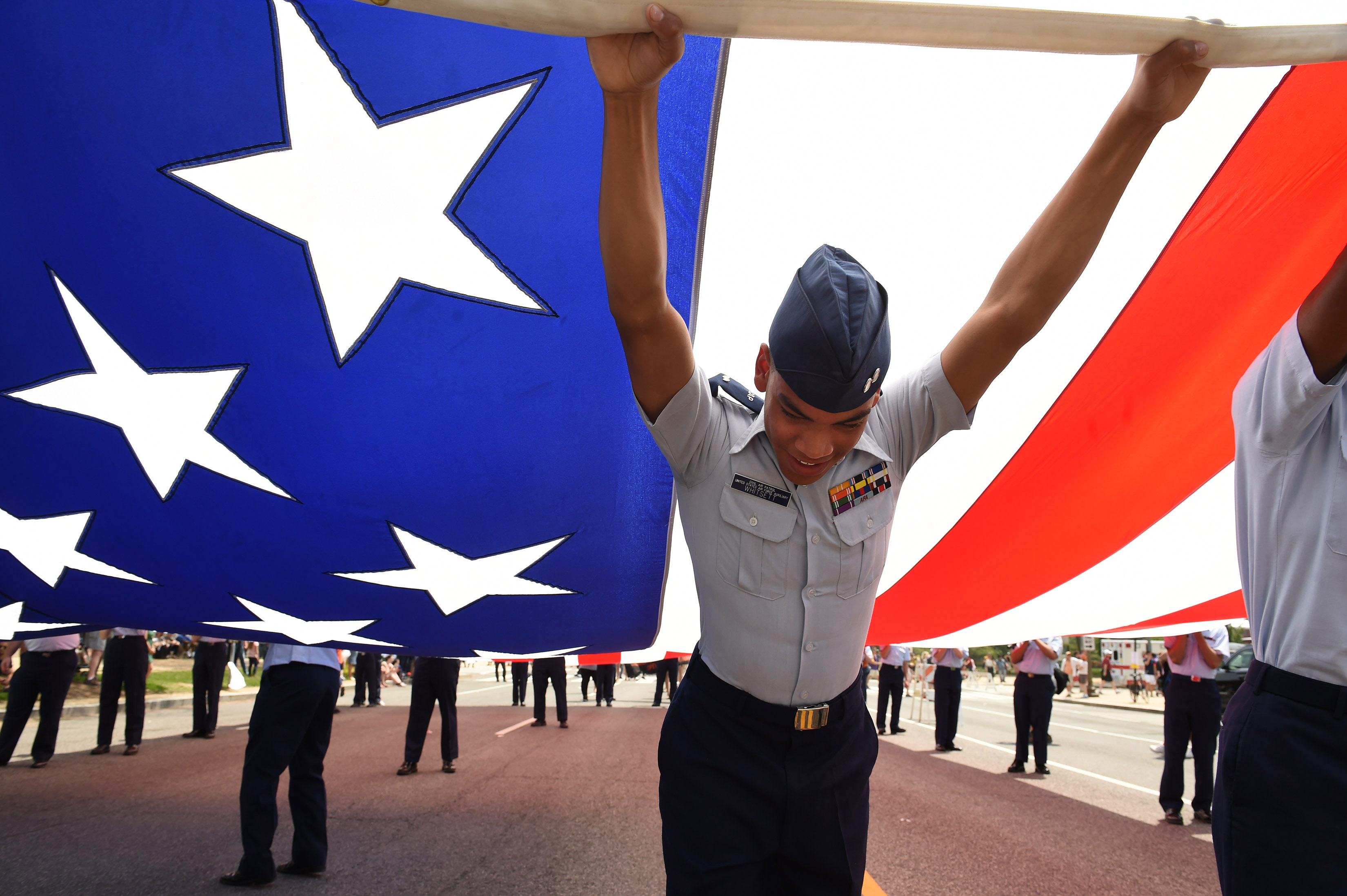 Tyler Whitsett, a First Lieutenant cadet with the Civil Air Patrol United States Air Force Auxiliary helps to hold up a large American flag prior to the start of the National Memorial Day Parade on May 25, 2015 in Washington, DC.