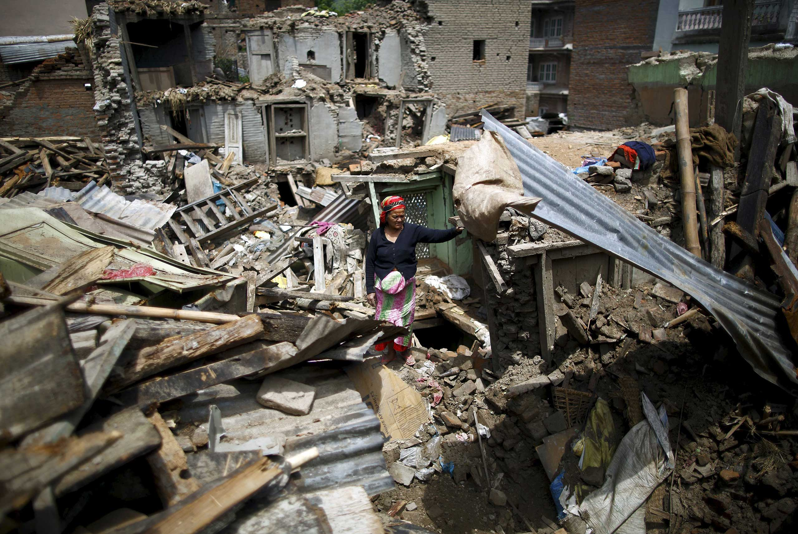 A woman stands on the debris of collapsed houses after a fresh 7.3-magnitude earthquake struck Nepal, in Sankhu on May 12, 2015.
