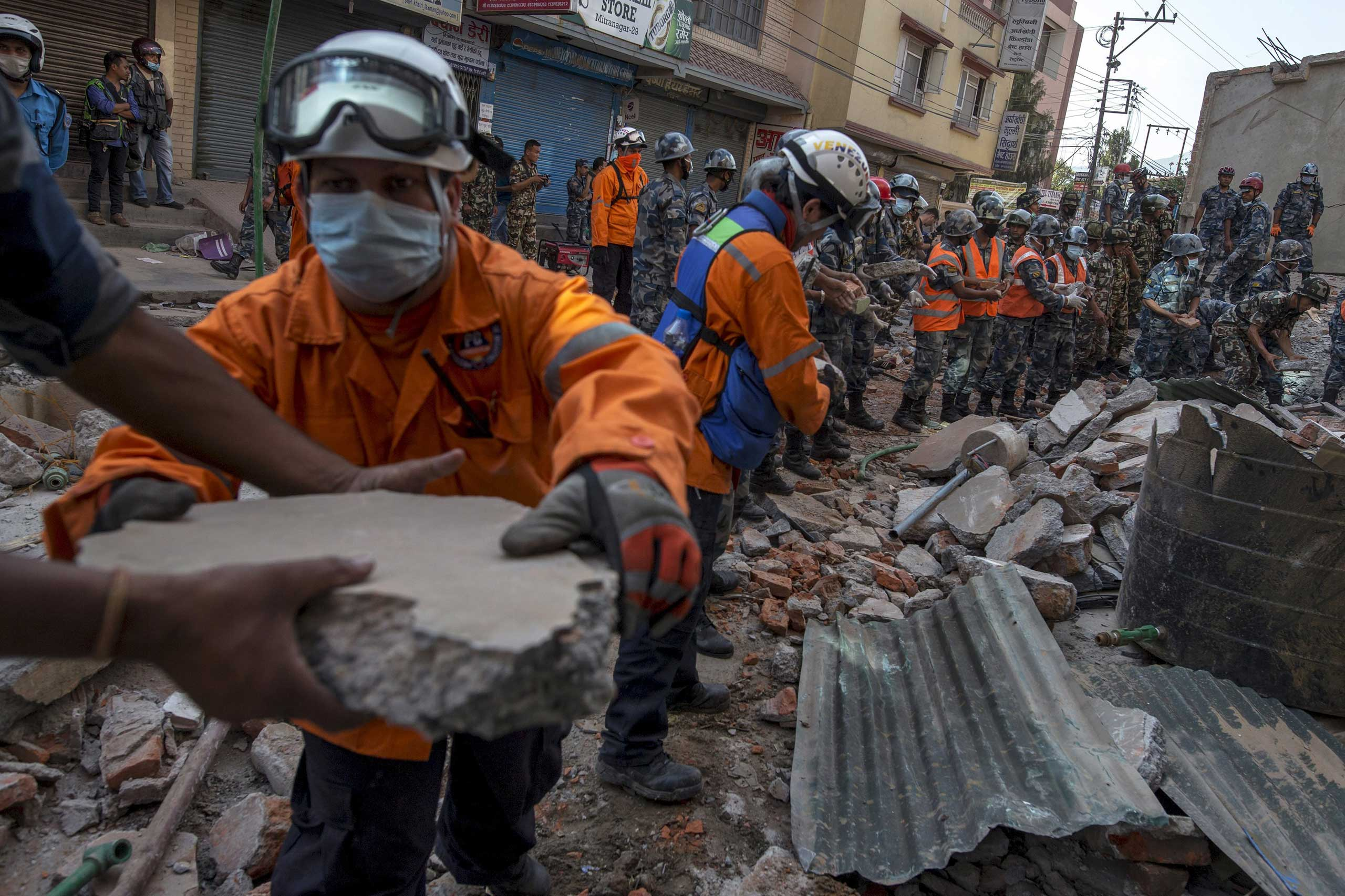 Nepalese military personnel remove debris in search of survivors after a fresh 7.3 earthquake struck, in Kathmandu on May 12, 2015.
